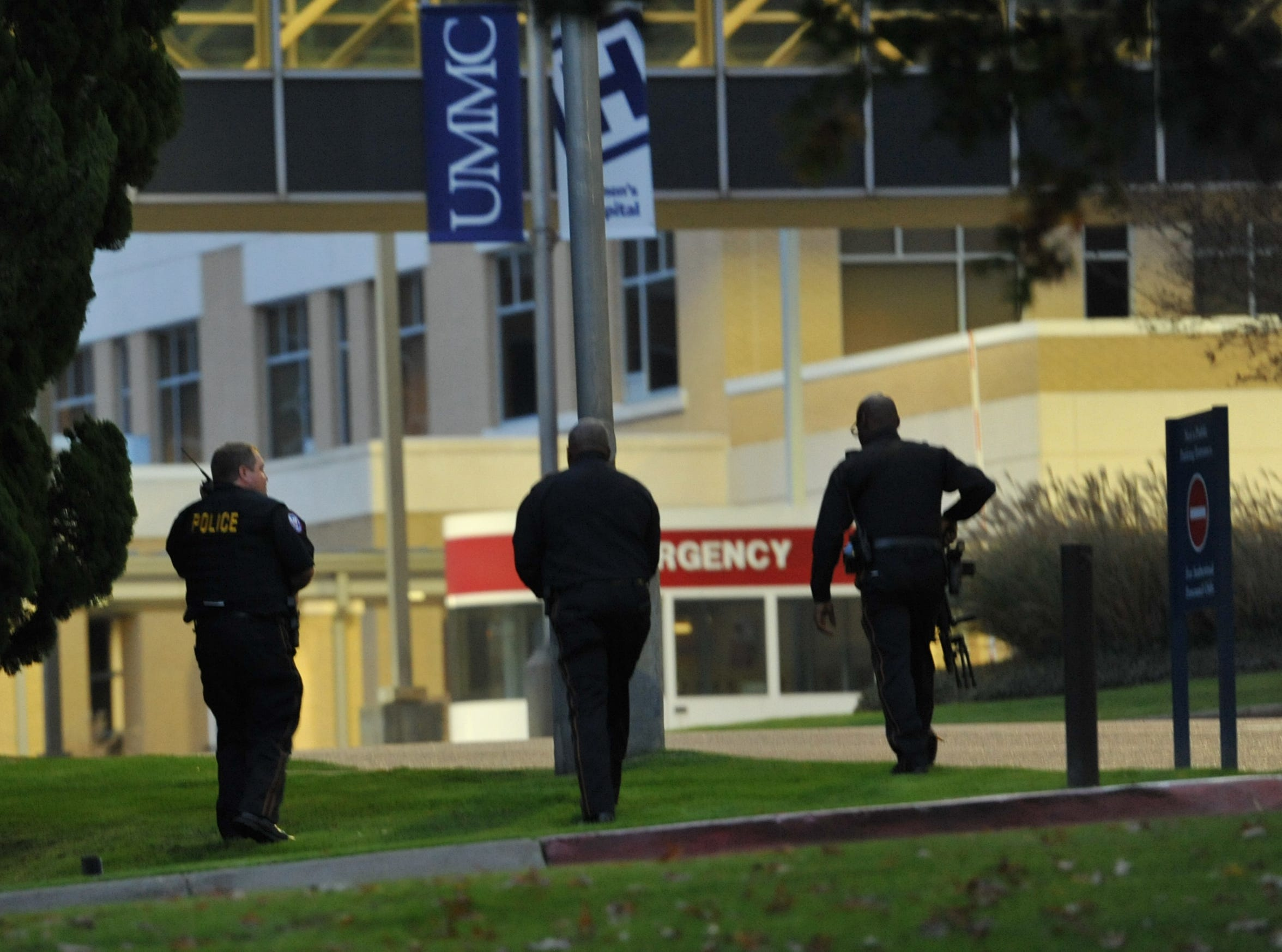 Heavily-armed Jackson police head around the backside of a parking garage during an investigation of a shooting in front of the UMMC campus Thursday night.