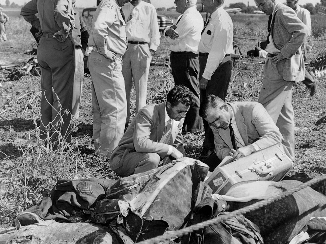 Lt. Col. Henry C.Leach, far left, of Ft. Knox, stands by as another officer watches two officials of Resort Airlines examine the log and other records recovered from wreckage of the plane that crashed at Standiford Field. The airline men, stooping, are: L.T. McNamara and Guy Tomberlin, right, both of Miami. some soldiers' luggage and clothing are shown.