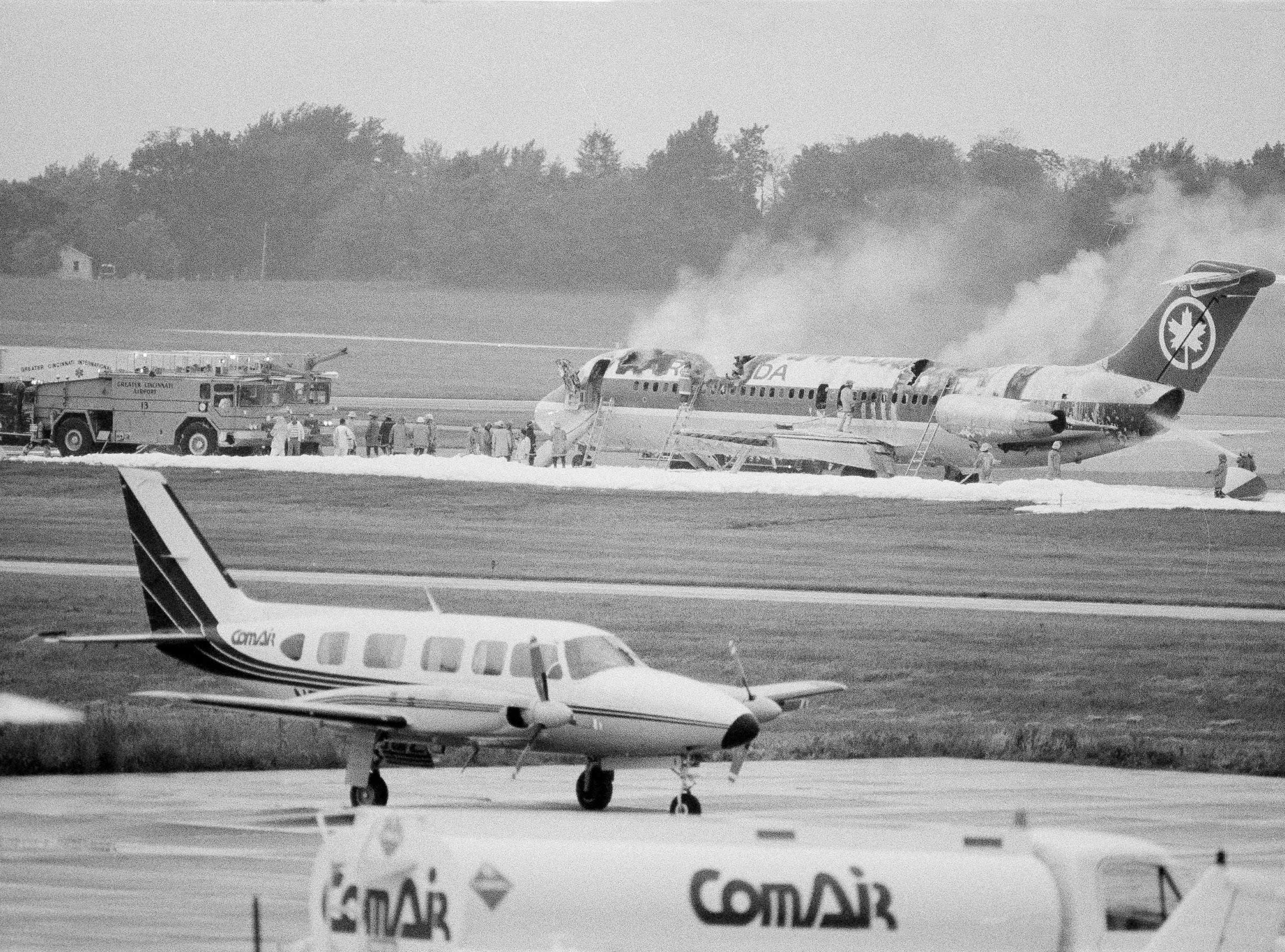 An Air Canada DC9 smolders at the end of a runway at Greater Cincinnati Airport, June 2, 1983. The plane caught fire and made an emergency landing in the middle of its scheduled flight from Dallas-Fort Worth to Toronto. There were two injuries reported, but no deaths. (AP Photo/Al Behrman)