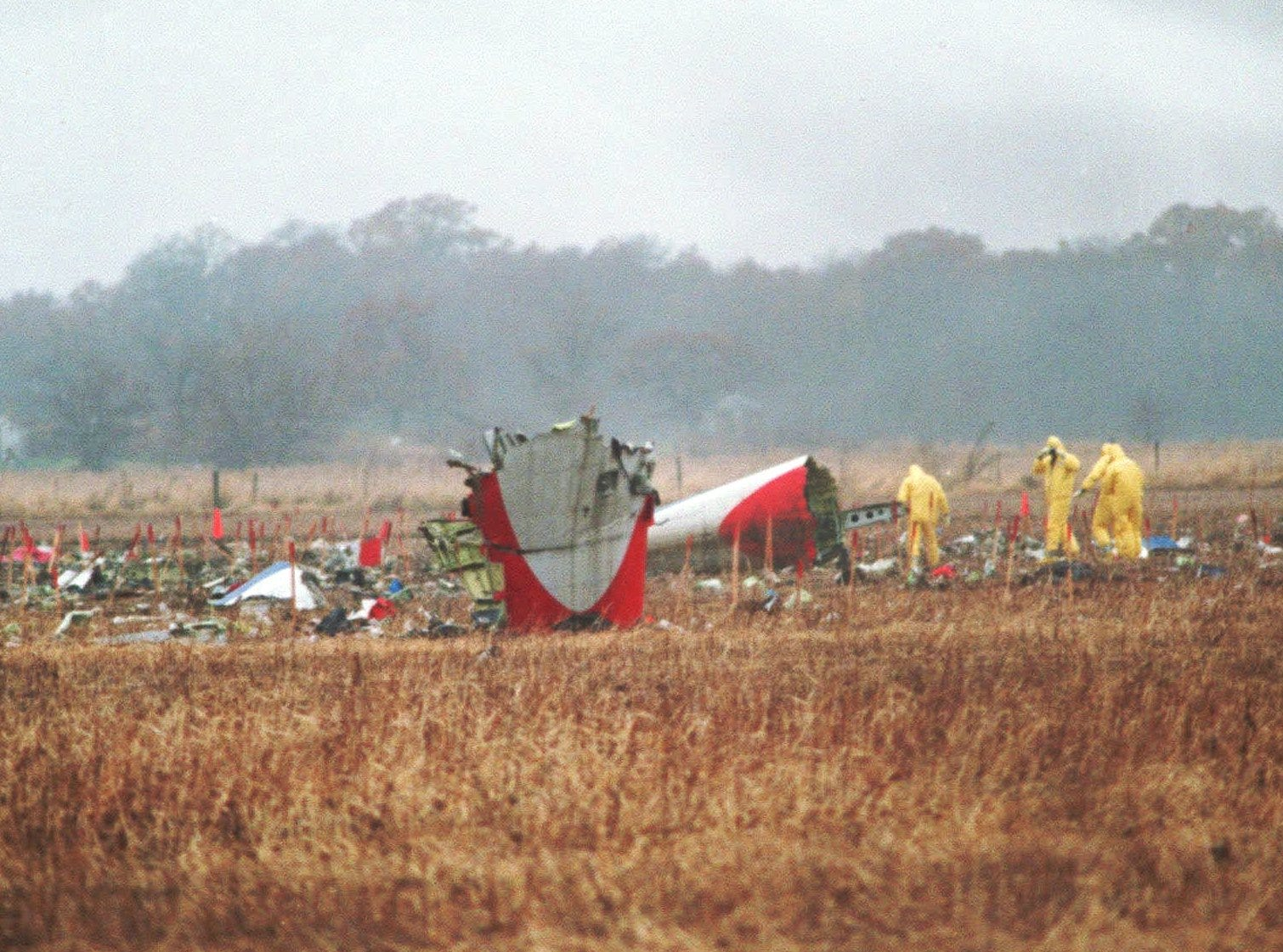 Investigators search the crash site of American Eagle Flight 4184 in a field near Roselawn, Ind., on Nov. 4, 1994. Families of some of the 68 people killed in the American Eagle crash settled their lawsuits with the airline and manufacturers of the airplane for $110 million on Monday, Sept. 22, 1997. Flight 4184, bound from Indianapolis to O'Hare International Airport, was in a holding pattern in a freezing rain the evening of Oct. 31, 1994, when it suddenly rolled and plunged to the ground. (AP Photo/POOL, Charles Bennett)
