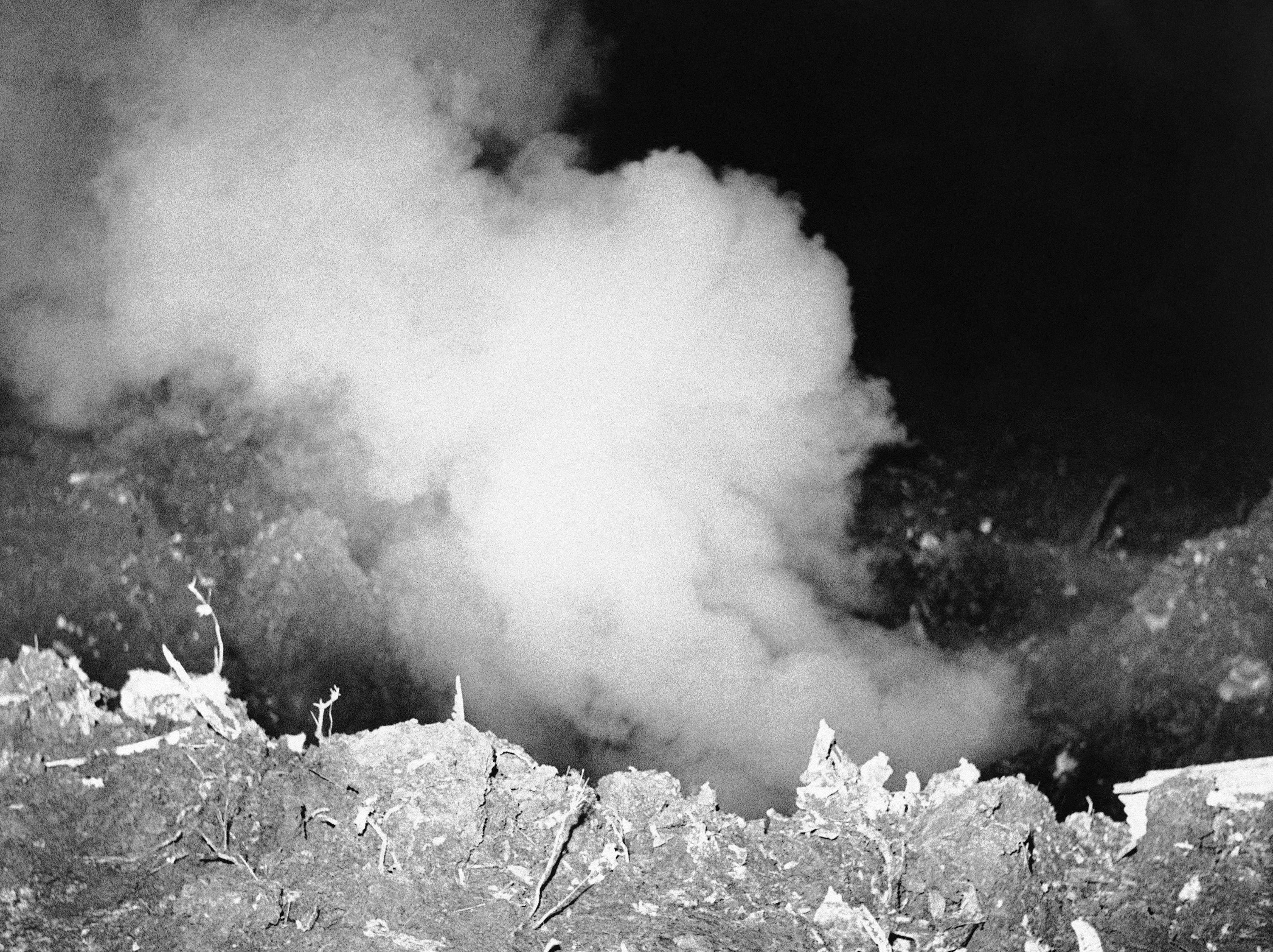 Smoke pours up from 20-foot-deep crater dug by fuselage of Northwest Airlines plane, March March 17, 1960 in Cannelton, Ind., six hours after crash. Crater, 30 feet across, contains debris and remains of 63 persons aboard. (AP Photo)