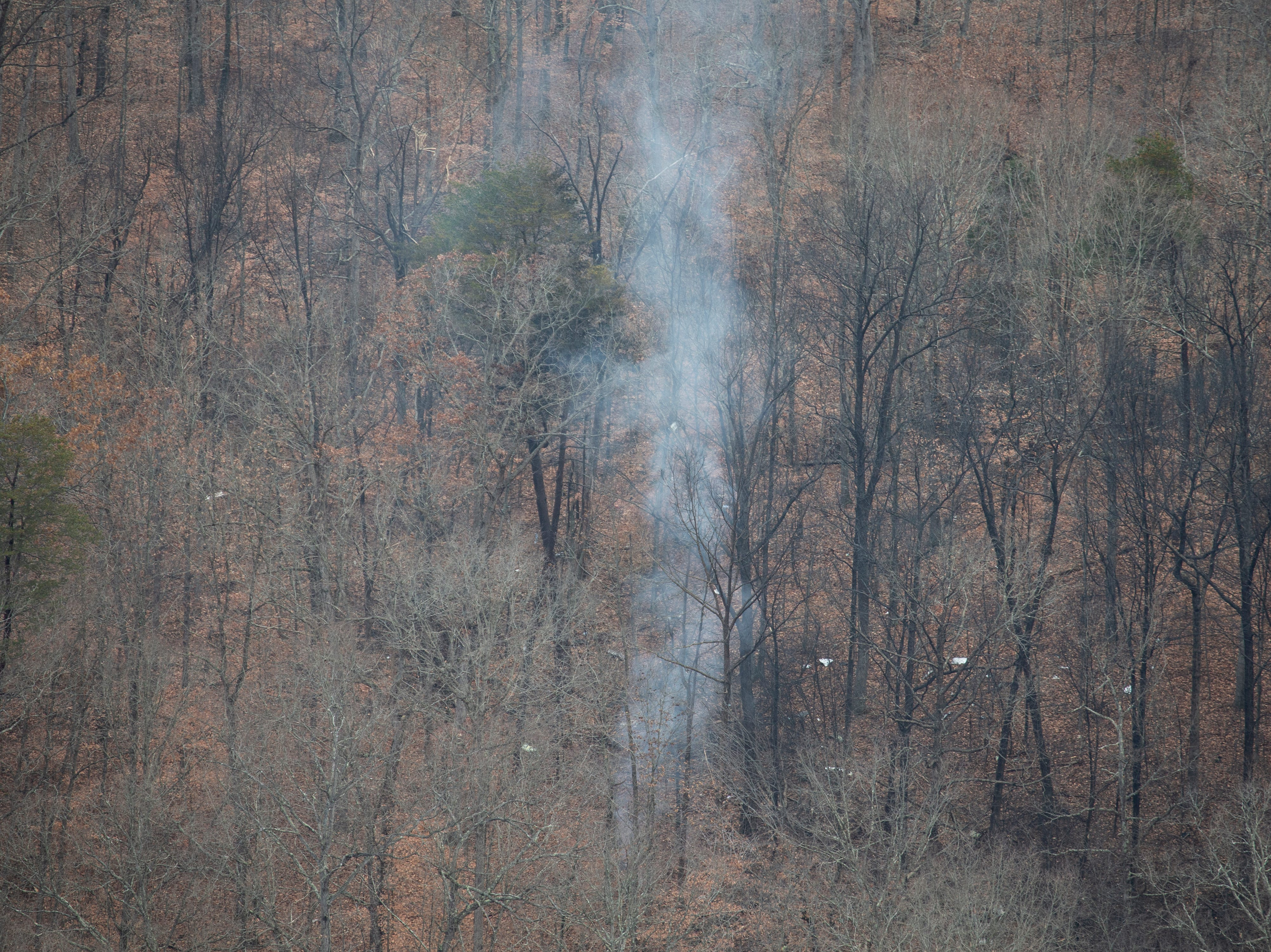 A plume of smoke and debris on the ground are the only indication of a small plane that crashed in a wooded area near Memphis, Indiana following a takeoff from the Clark County Airport. Nov. 30, 2018.