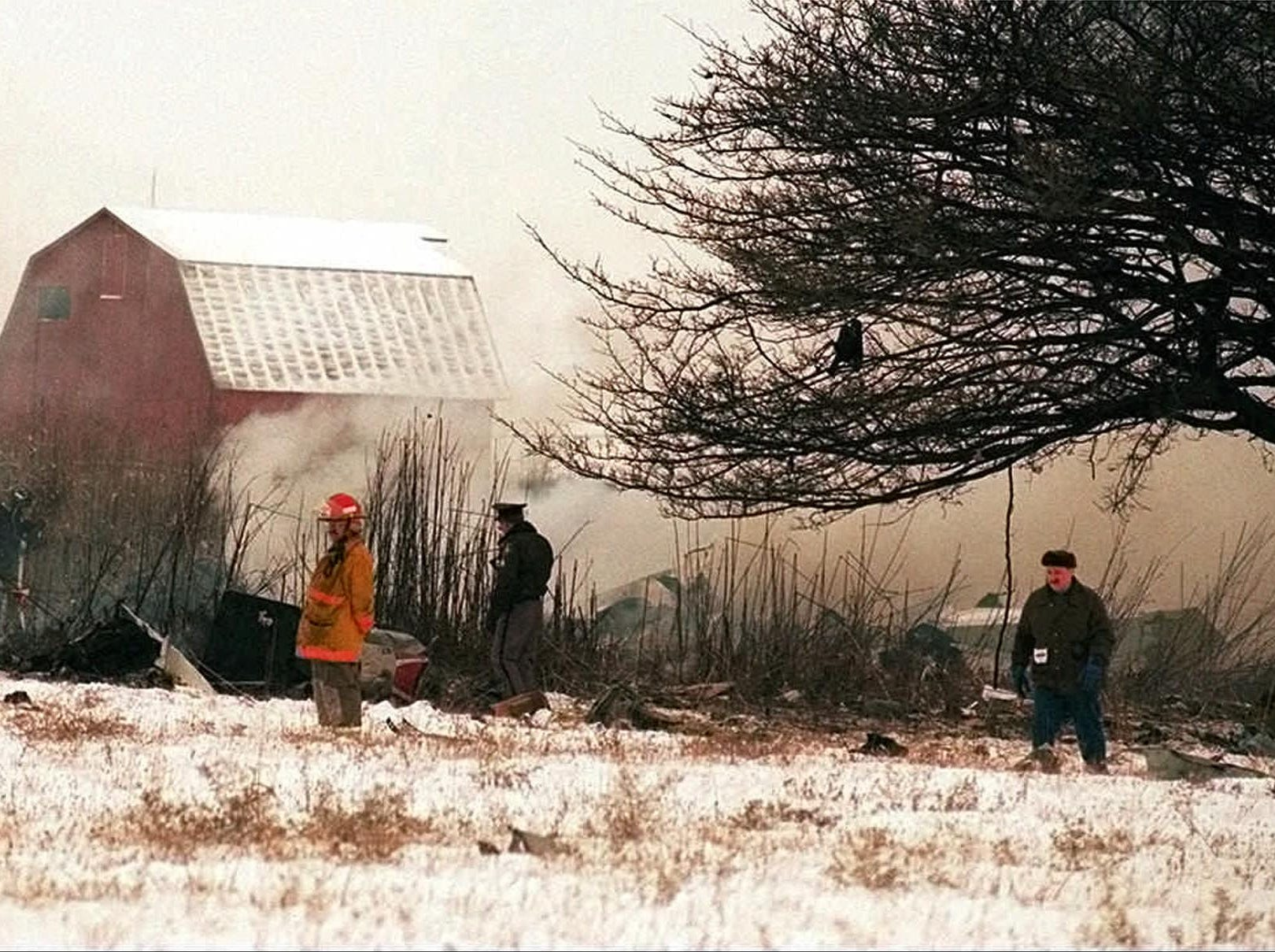 Rescue workers search the wreckage of a Comair Inc. commuter plane that crashed in overcast weather near Monroe, Mich., on Thursday, Jan. 9, 1997, on a flight from Cincinnati to Detroit, killing all 29 aboard. The 30-seat plane splintered into small pieces, leaving a black patch on a clearing in the snow. (AP Photo/The Monroe Evening News, Lynden Steele)
