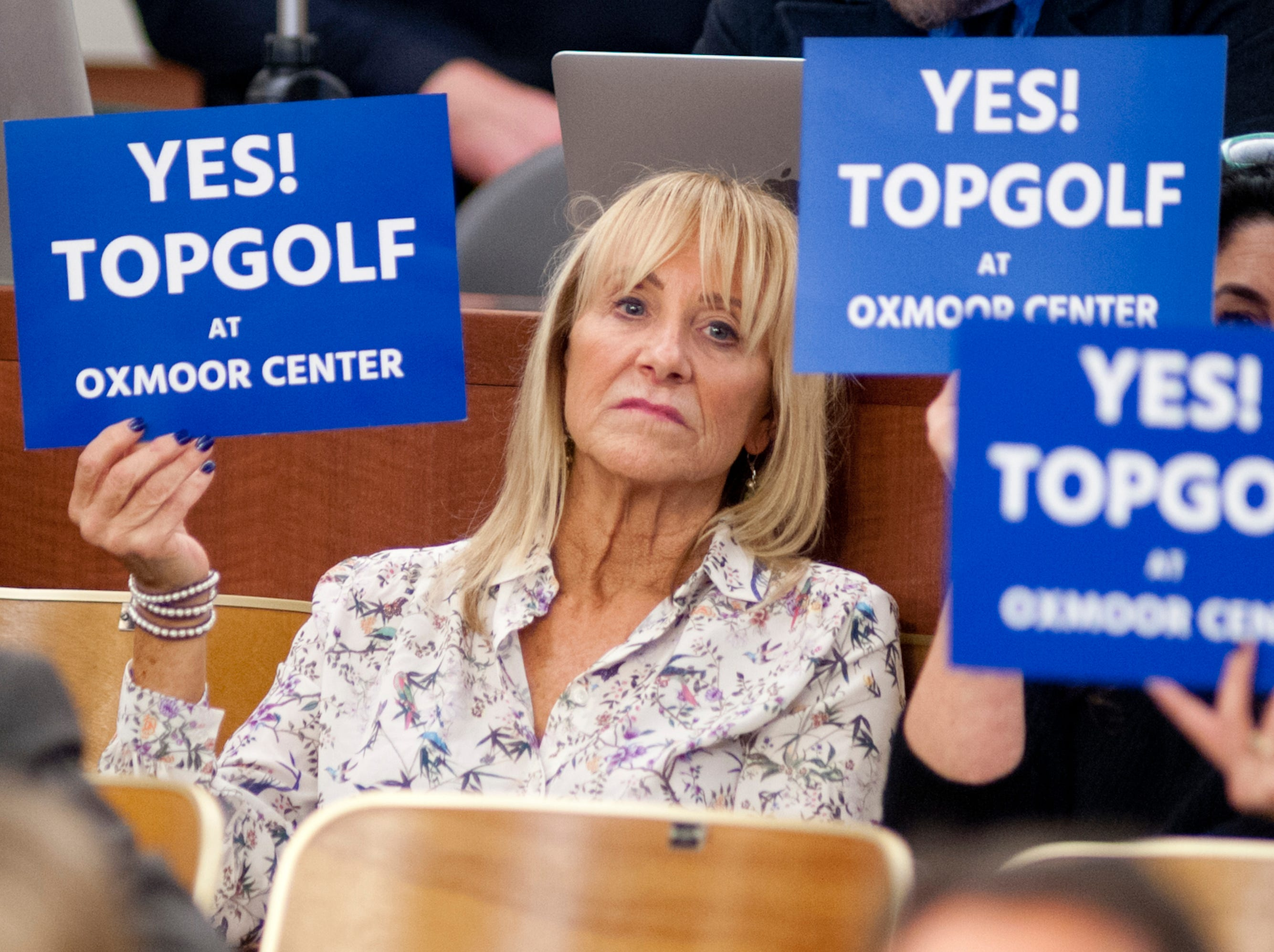 Supporters of Topgolf at Oxmoor Center hold up placards during the debate on approving the planning commission's recommendations on Nov. 29, 2018.