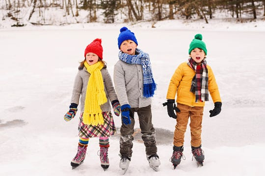 Three children on ice skates.