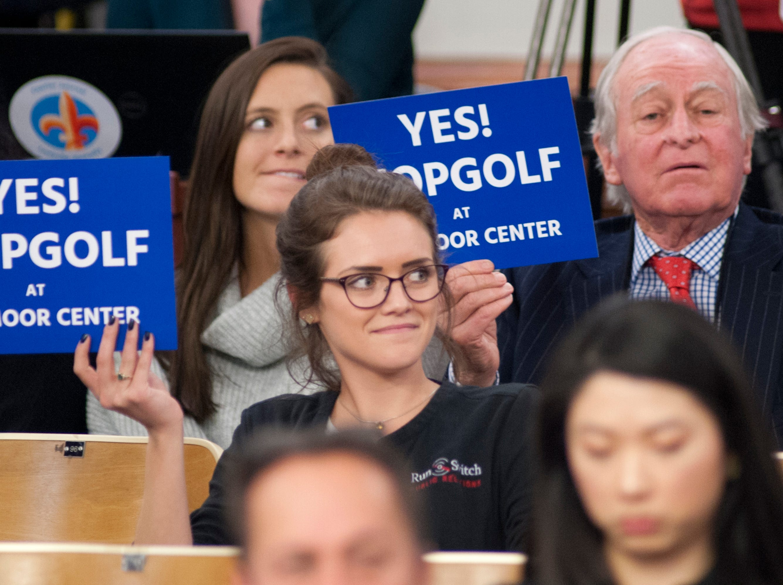 Supporters of Topgolf at Oxmoor Center, including Tia Chancellor, center, account executive for RunSwitch Public Relations, (who represents Topgolf), hold up placards during the debate on approving the planning commission's recommendations on Nov. 29, 2018.