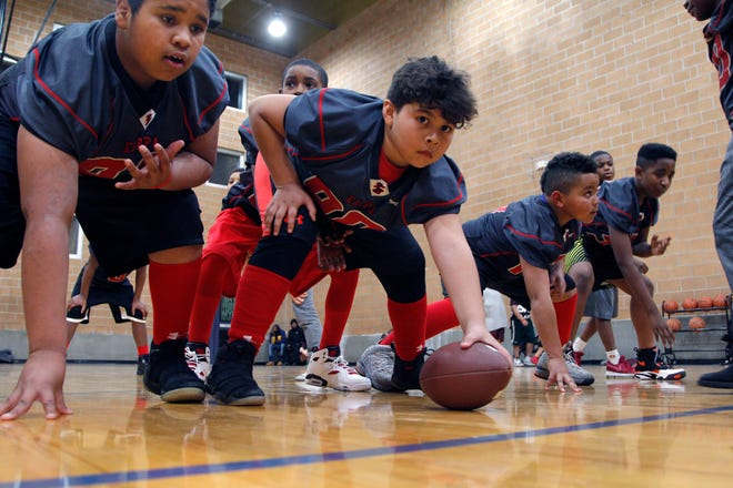 Kappa Express center Raymond Ruiz Jr. snaps the ball to quarterback Brandis Ardister during a Nov. 28 practice inside the RA1 Basketball Range in Lansing. The Kappa program started 43 years ago.