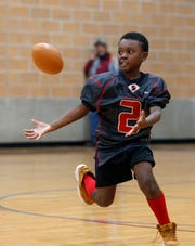 Kappa Express receiver John Parker catches a pass Nov. 28 during an indoor practice at the RA1 Basketball Range in Lansing. The Express, a 9-and-under team, are 16-0 this season.