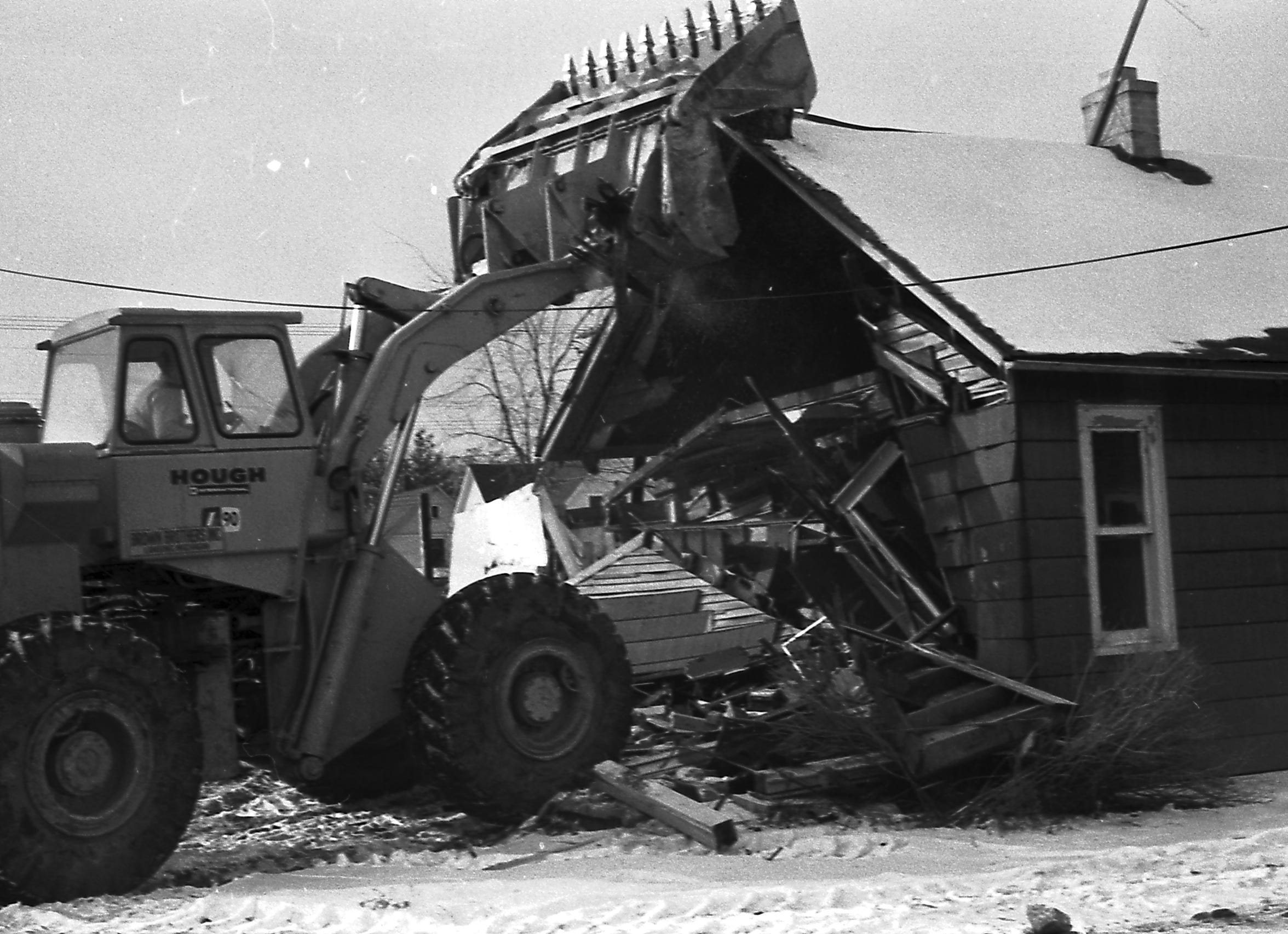 A home at Main and Logan streets is crushed in 1966 as part of the connector route clearance for Interstate 496.