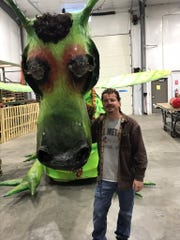 "Ryan LaSee an operator of ""Puff"" the Magic Dragon stands next to the 11-foot tall float."