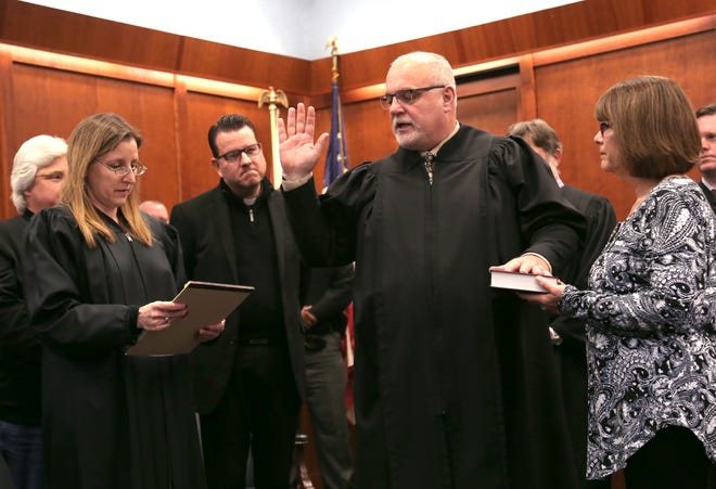 Judge Phil Naumoff is sworn in by Heather Cockly with his wife by his side inside of the Richland County Courthouse on Friday.