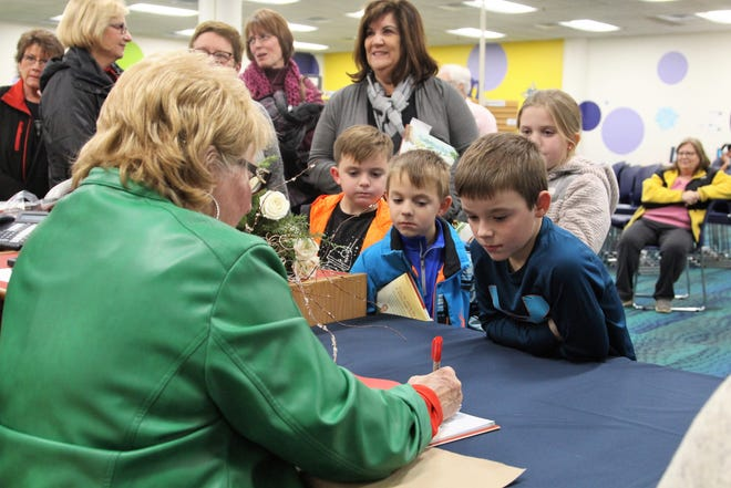 """Local author Shary Williamson signs a copy of her latest book """"A Magical Tale of Winter"""" for young fan Cooper Hardwick at the Marion Public Library on Thursday."""