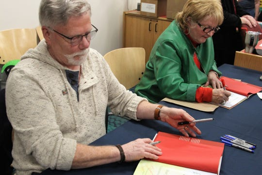 "Illustrator Jay Johnston signs copies of the fourth installment in ""The Woodland Elves"" series alongside local author Shary Williamson on Thursday."