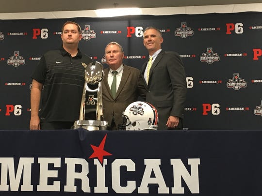 UCF coach Josh Heupel, AAC commissioner Mike Aresco and Memphis coach Mike Norvell pose with the AAC championship game trophy Friday during the pregame press conference.