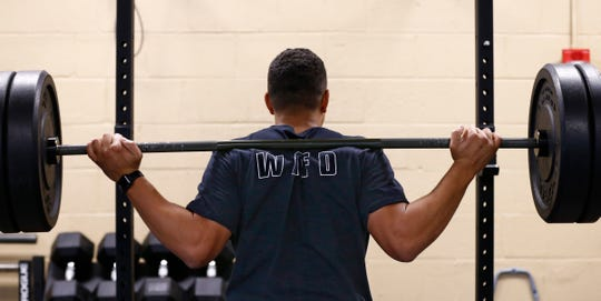 Tony Bilderback lifts a barbell for squat exercises as part of his physical training regiment to perform at peak with the West Allis Fire Department. Bilderback will arrive at Station 2 well before the 8 a.m. start of a 24-hour shift to exercise.