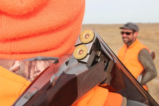 A shotgun is held over the shoulder of a hunter during a break in a pheasant hunt near Aberdeen, South Dakota.