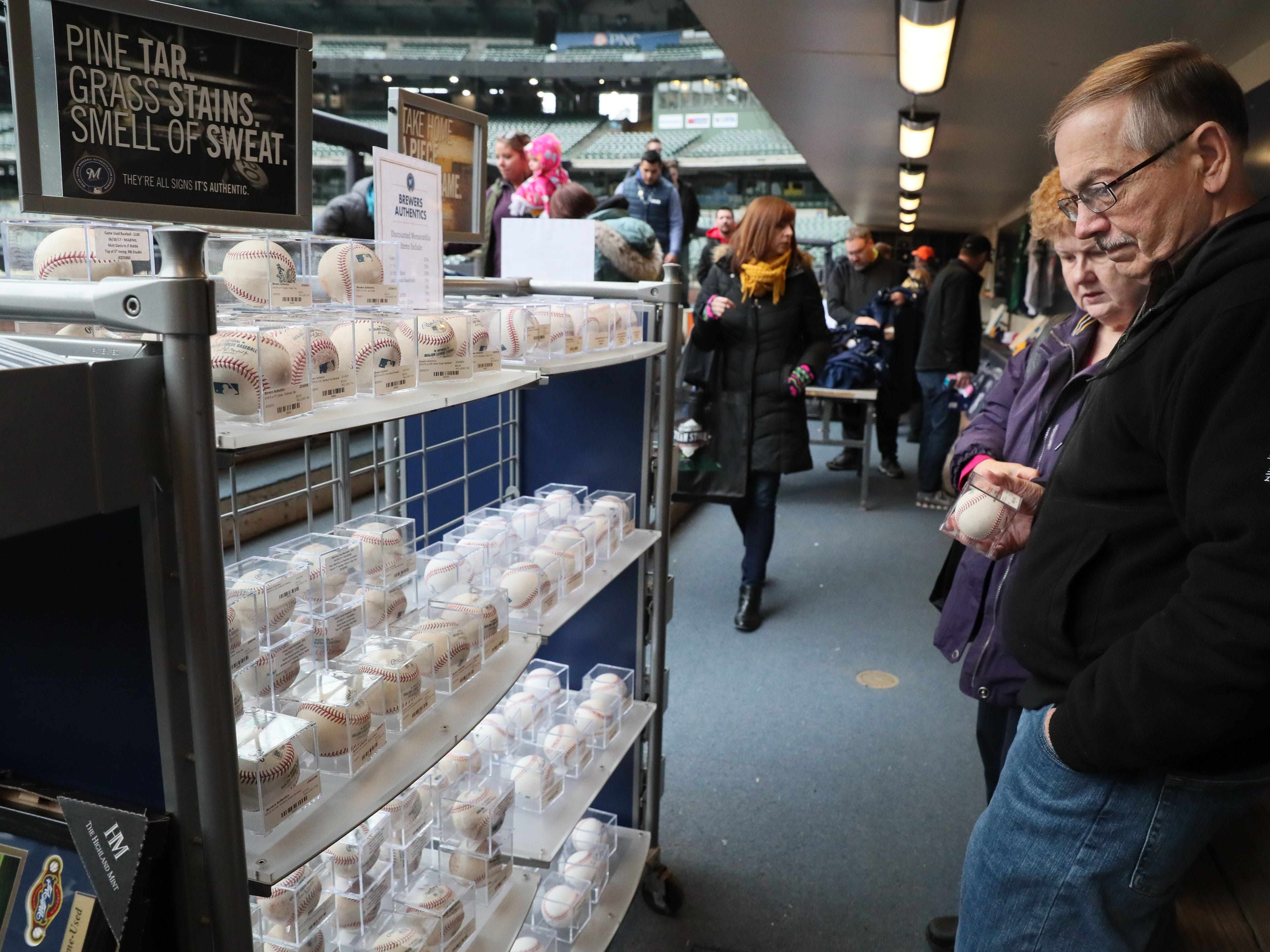 Bill Streicher of Greenfield and his wife, Cindi, check out the choices of game balls for sale at the clubhouse sale at Miller Park.