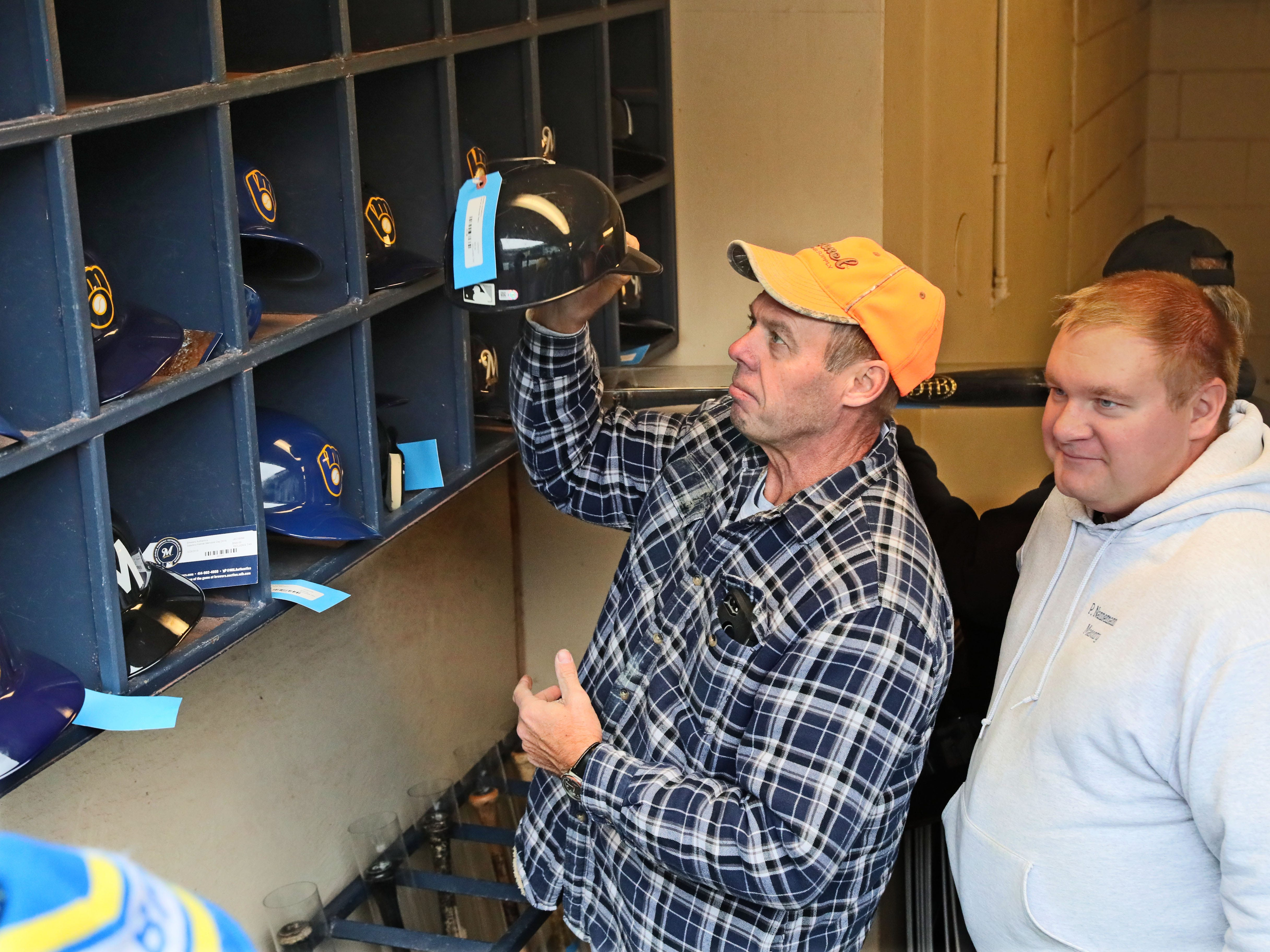 Jim Nannemann (left) and his son Joshua Nannemann, both of Waterford, look at used batting helmets from various games and players that are being sold.