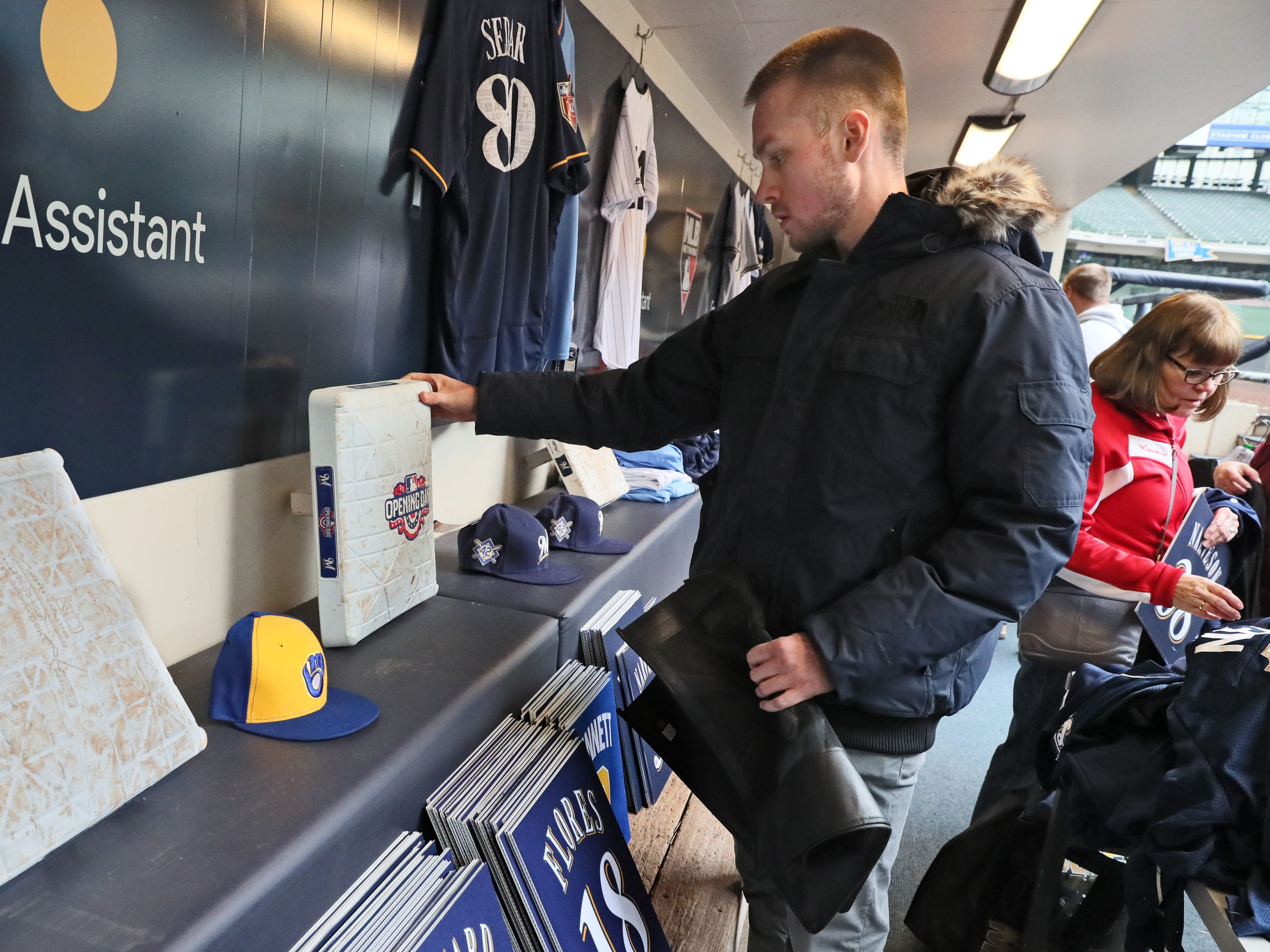 Michael Theile of Milwaukee looks over a third base that was used on opening day that is for sale. The Milwaukee Brewers are having their two-day annual clubhouse sale in the visitors' clubhouse and dugout. Hours are 8 a.m. to 8 p.m. Friday and Saturday.
