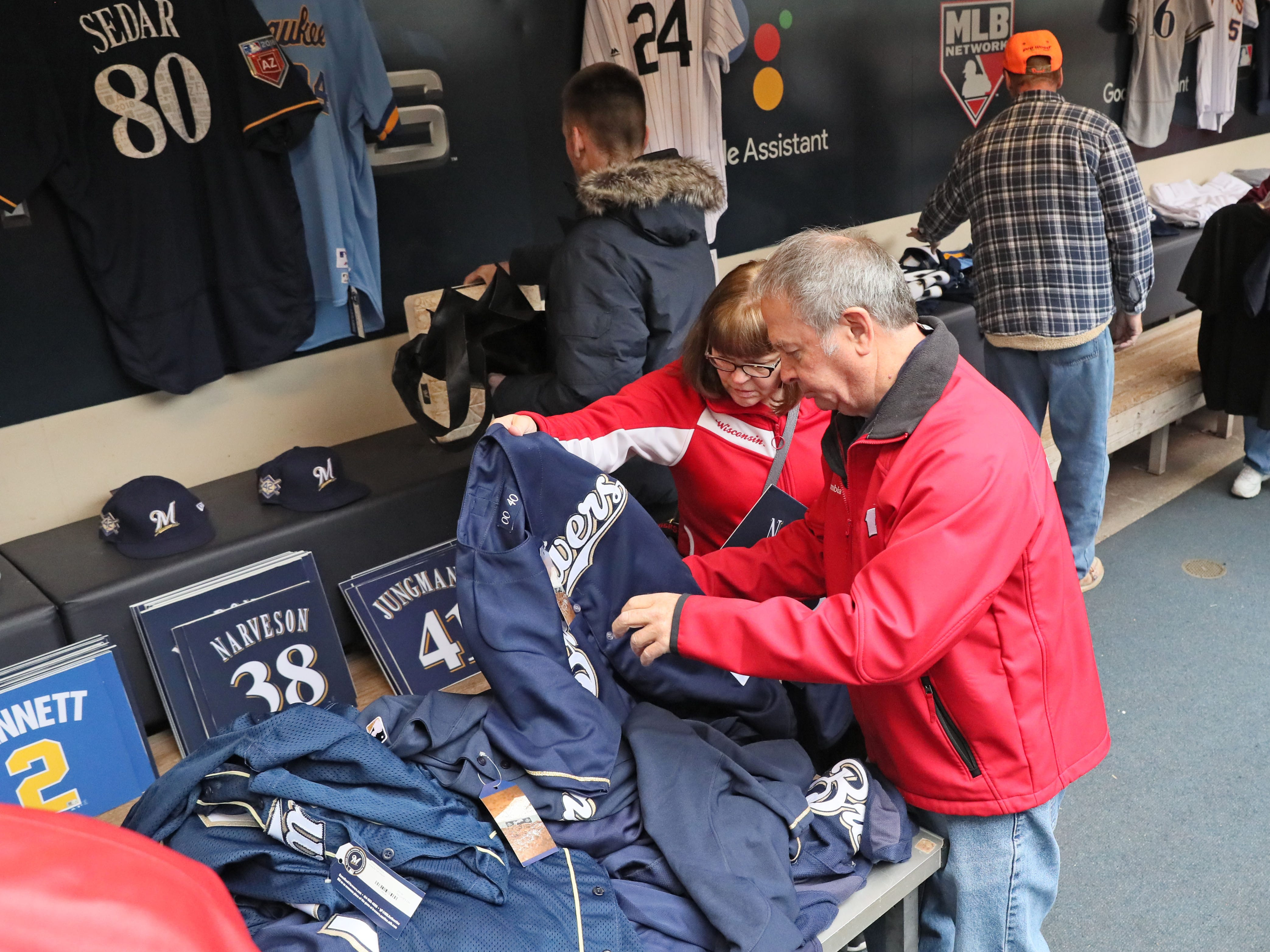 Linda Govier and her husband, Randy,  of Franklin peruse unmarked game jerseys for sale.  The players wore them but it's not known which ones. Most  likely were worn in spring training.