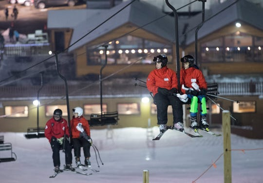 Skiers ride a chairlift Thursday at Little Switzerland ski area in Slinger.