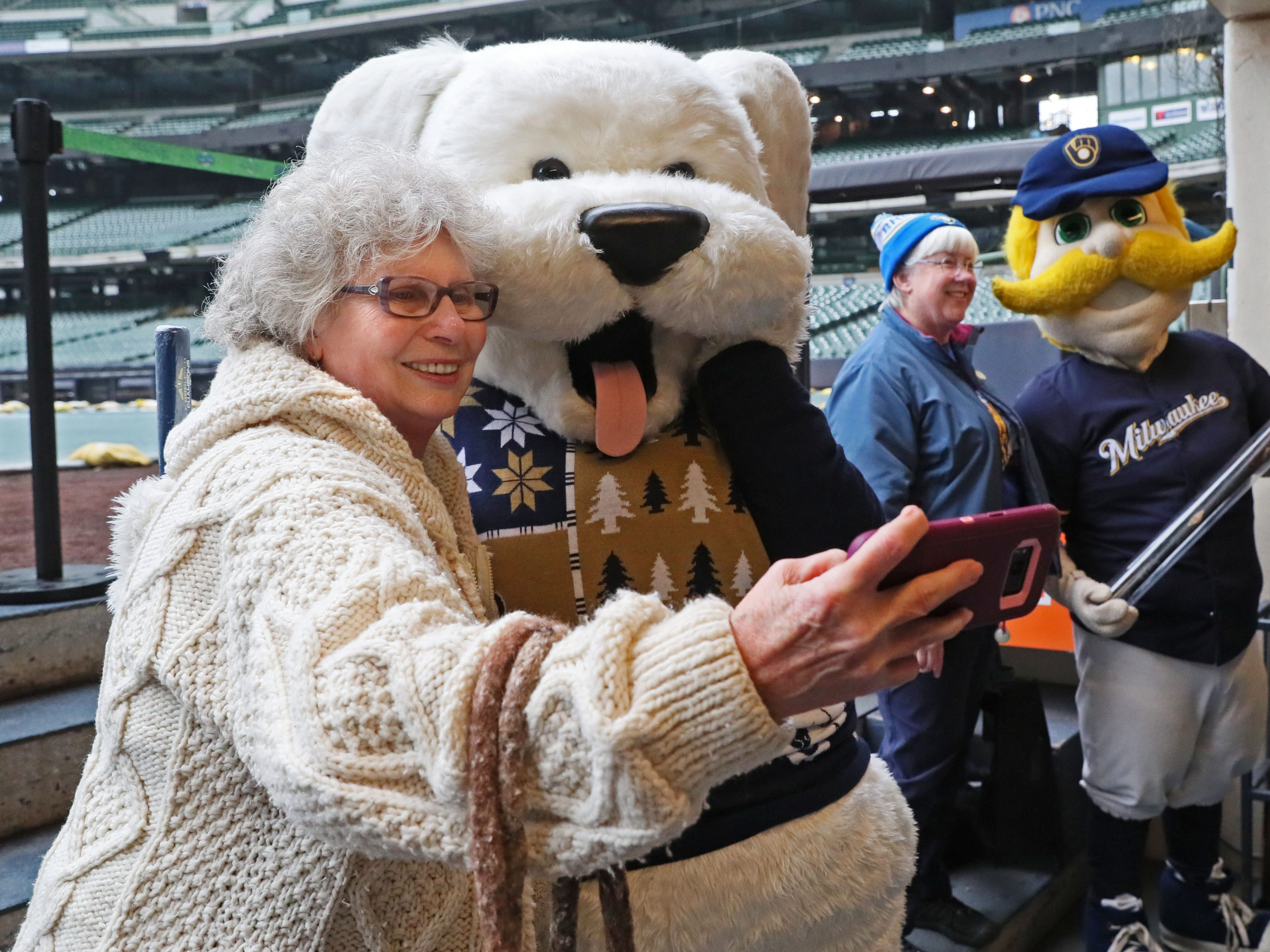 Paula Gutmanis of Franklin lines up a selfie with a mascot of Hank, the Brewers' team dog, while in the background, Laura Hemming of Madison poses for a photo with Bernie Brewer.