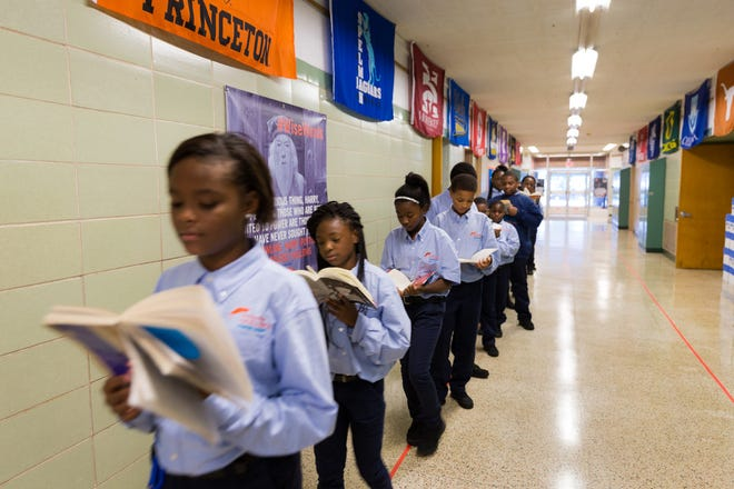 Uniformed students at Milwaukee Excellence Charter School make hallway time productive by keeping up with their reading.