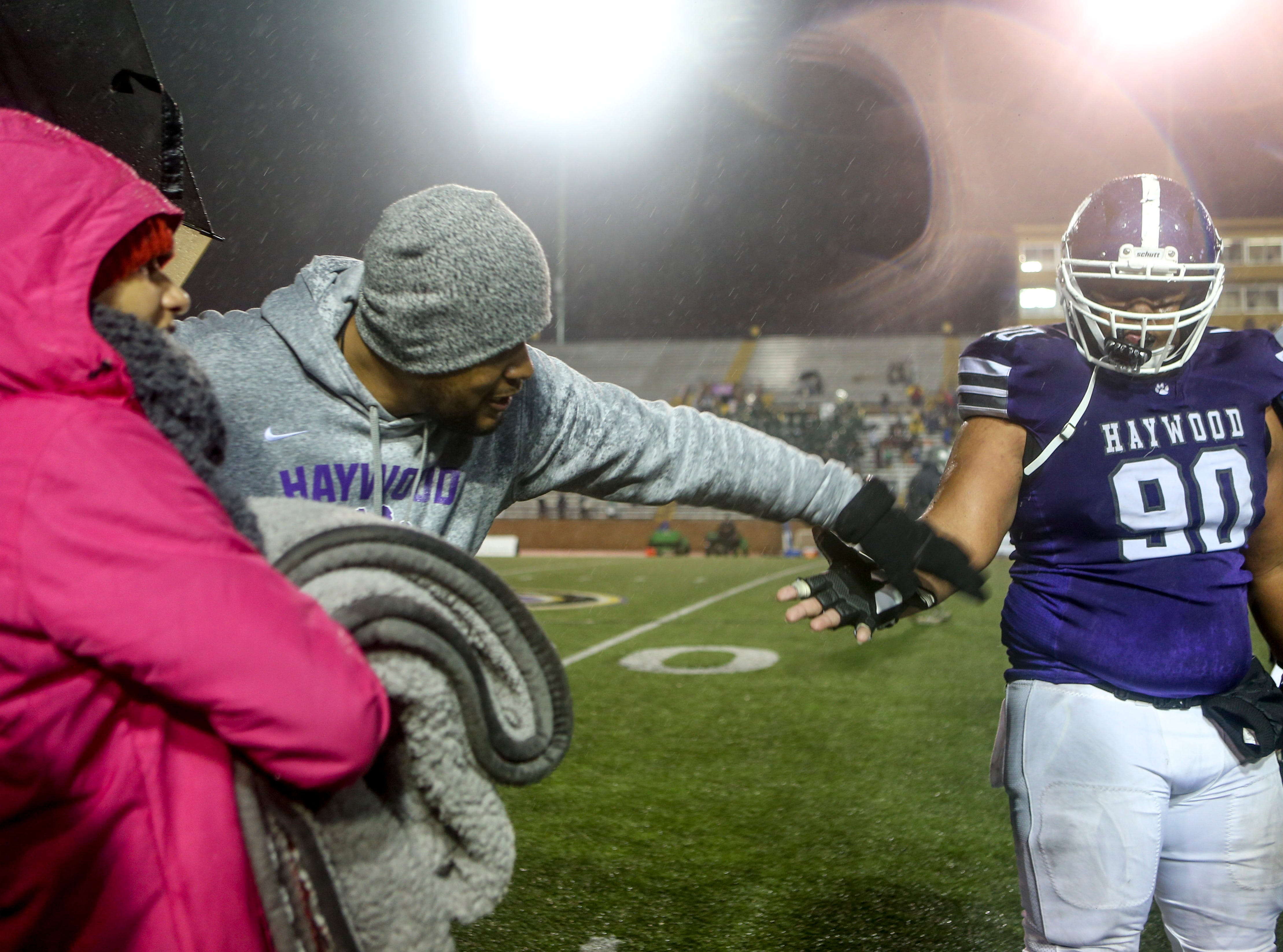 Steve Hookfin reaches out to high five Haywood's Emanuel Beard (90) while speaking with his family during the Class 4A Blue Cross Bowl between Haywood and Greeneville at Tennessee Tech's Tucker Stadium in Cookeville, Tenn., on Thursday, Nov. 29, 2018.