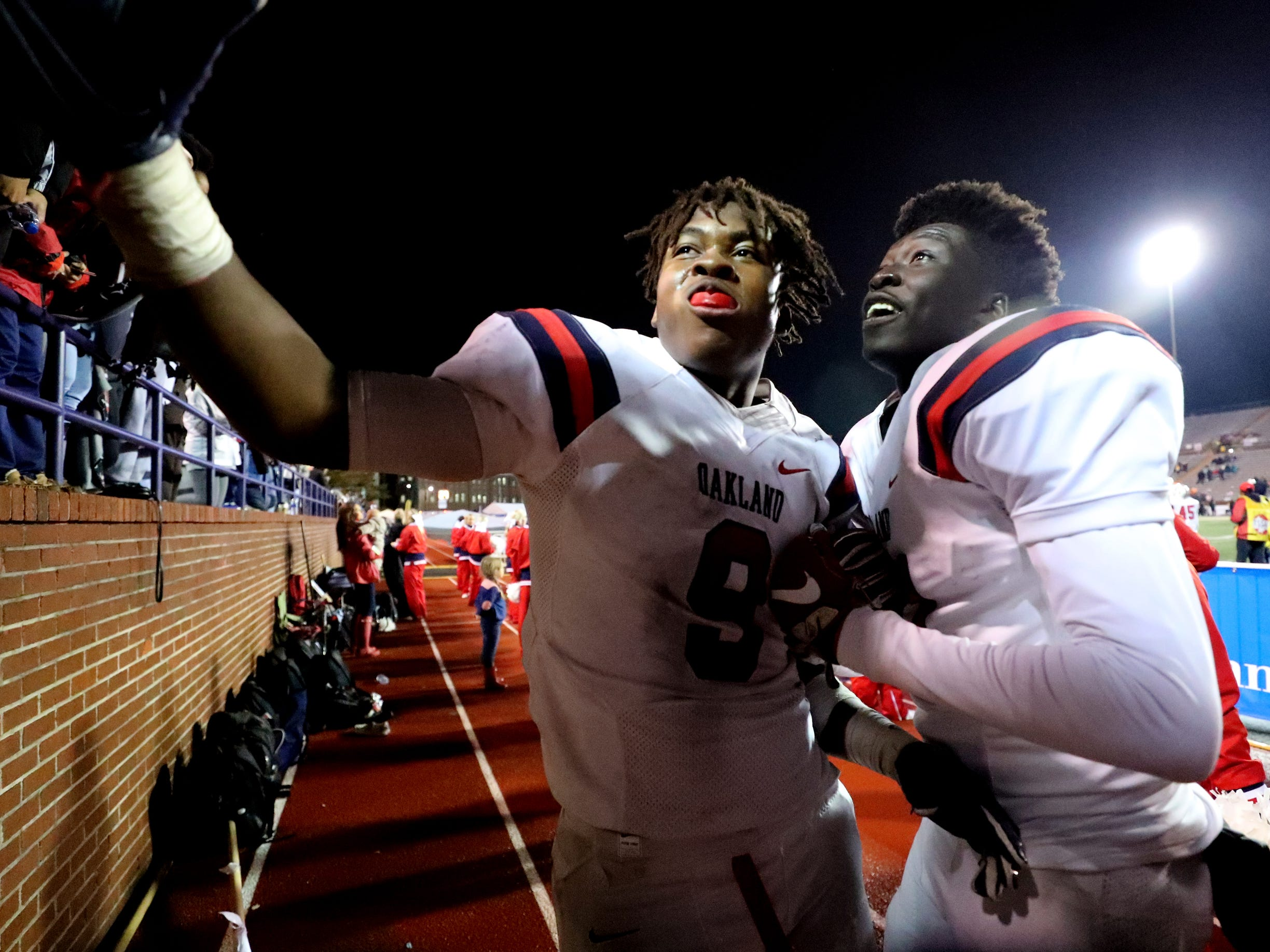 Oakland's Tekoy Randolph (9) and Dixon Luwaju (81) celebrate with the fans late in the 4th quarter of the game against Whitehaven during the 6A State Championship BlueCross Bowl game on Thursday, Nov. 29 2018.