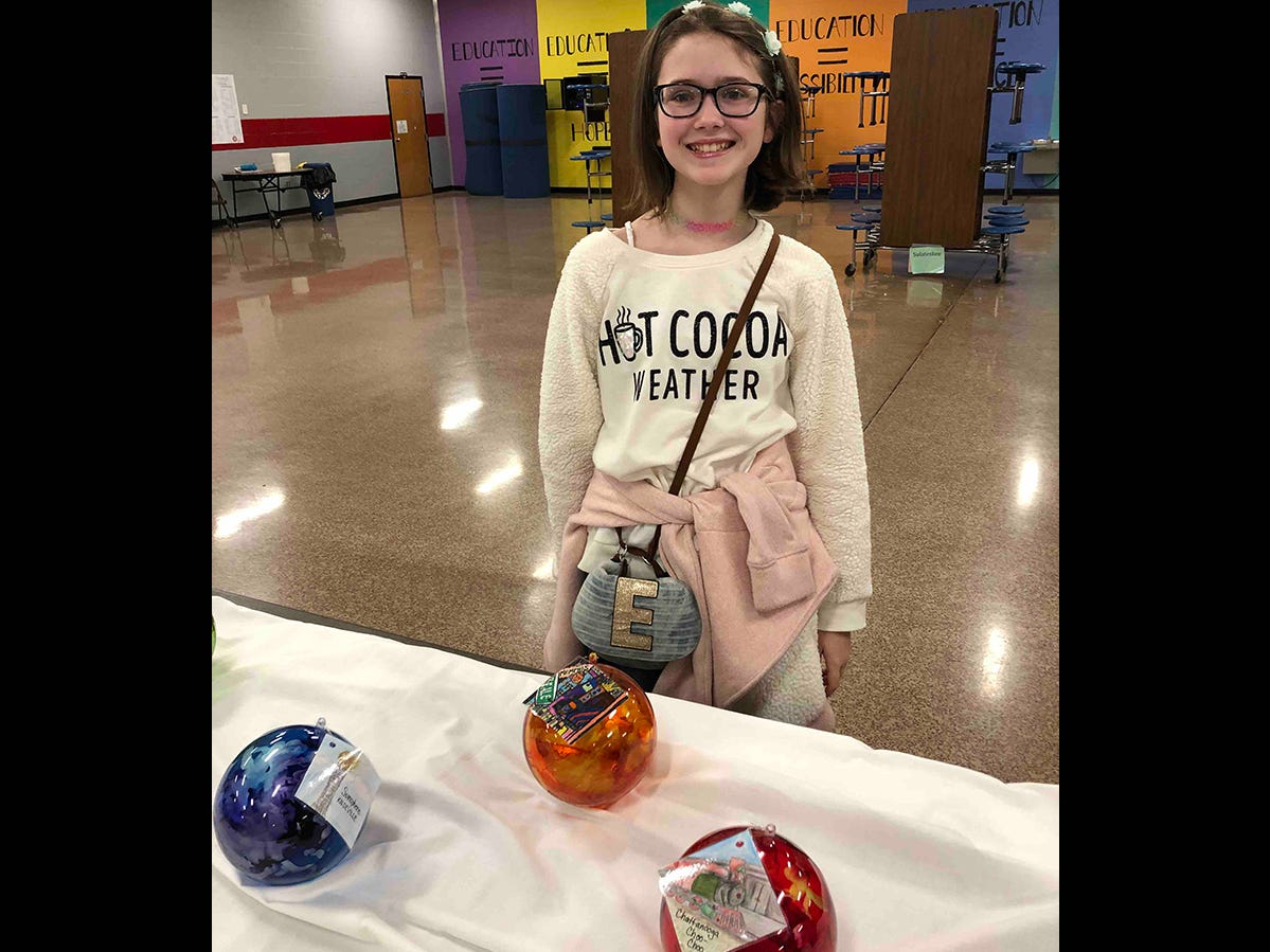 Emma Higdon, a sixth grader at Fairview Middle School, reveals her ornament for Beale Street in Memphis.