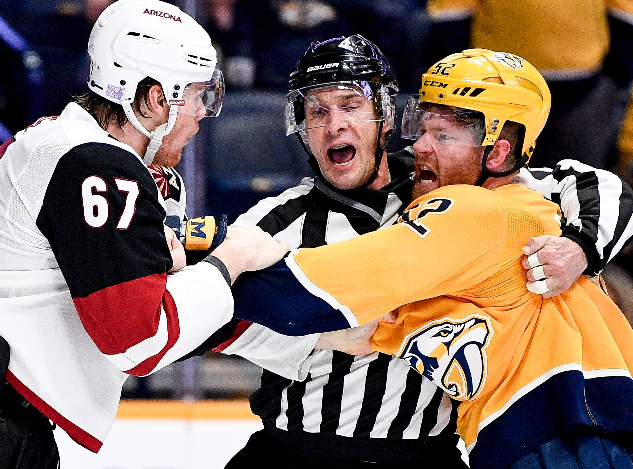 Linesman Ryan Galloway (82) breaks up a fight between Arizona Coyotes left wing Lawson Crouse (67) and Nashville Predators defenseman Matt Irwin (52) during the third period at Bridgestone Arena in Nashville, Tenn., Thursday, Nov. 29, 2018.