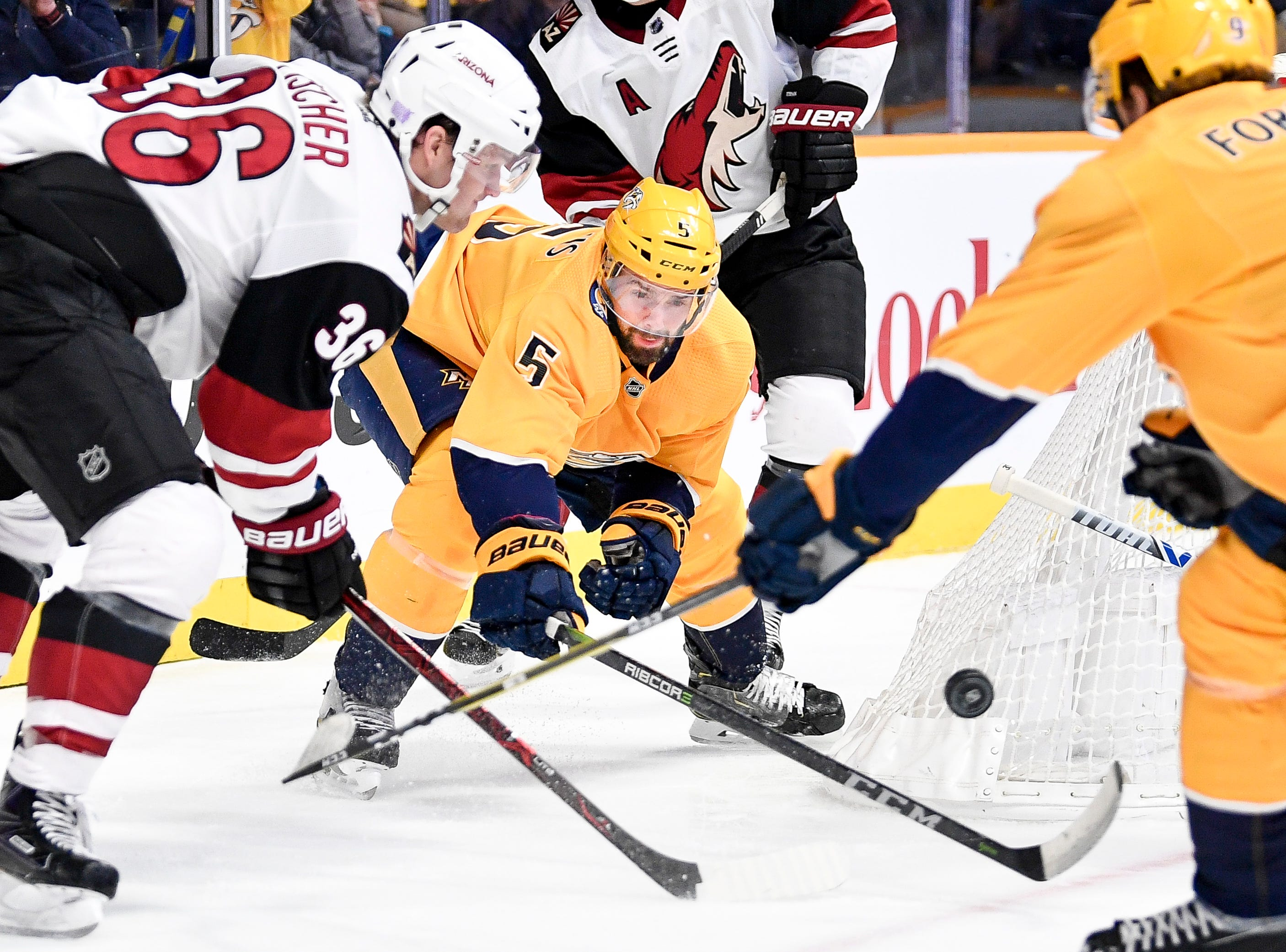 Nashville Predators defenseman Dan Hamhuis (5) leans in for the puck against Arizona Coyotes right wing Christian Fischer (36) during the second period at Bridgestone Arena in Nashville, Tenn., Thursday, Nov. 29, 2018.