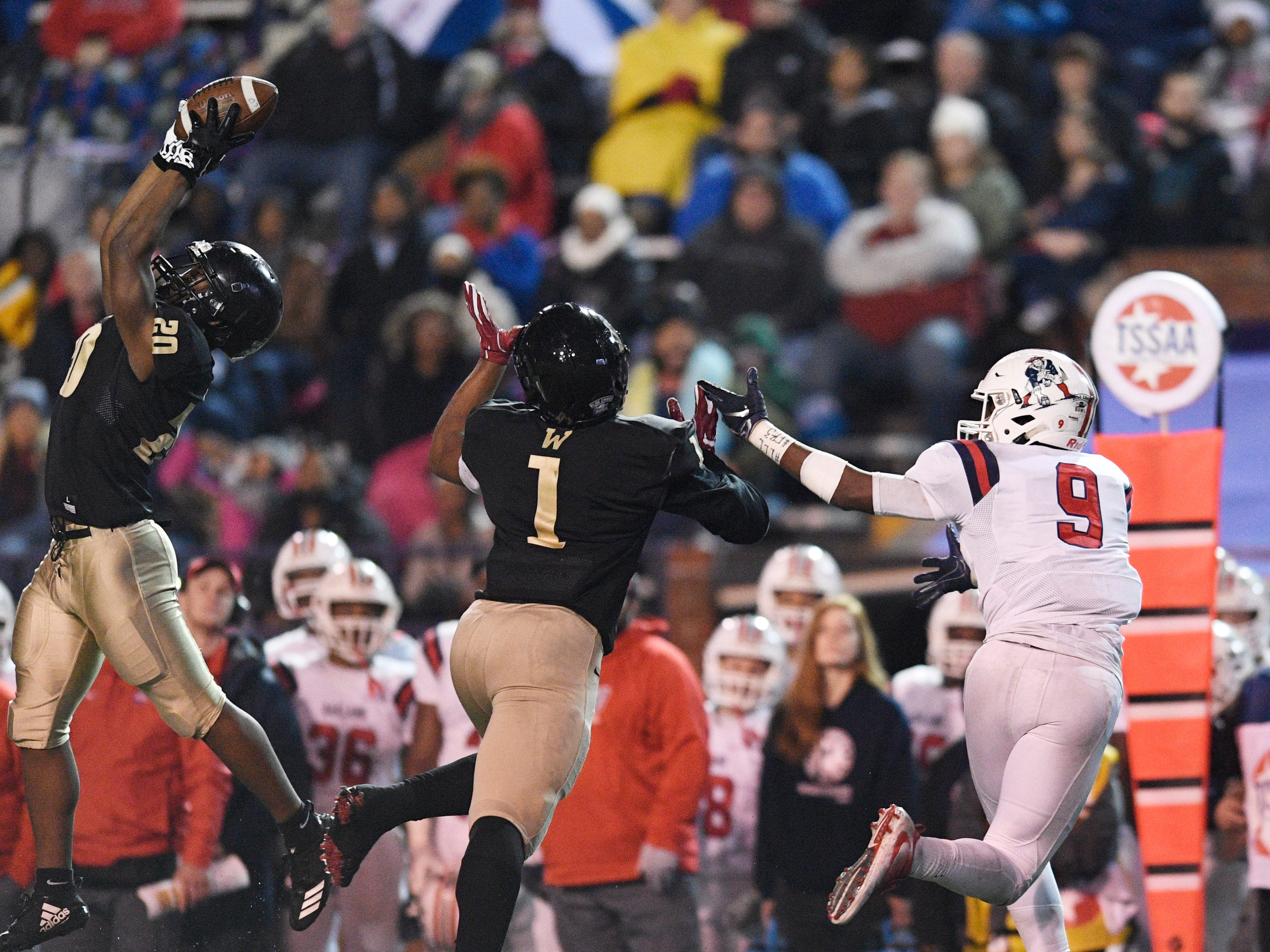 Whitehaven Jamal Frazier (20) goes up high for an interception in the second half in front of Whitehaven's Bryson Eason (1)  and Oakland's Tekoy Randolph (9) at the Class 6A BlueCross Bowl state championship at Tennessee Tech's Tucker Stadium in Cookeville, Tenn., on Thursday, Nov. 29, 2018.
