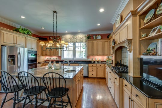 The home's kitchen has an abundance of natural light and a large island with eat-in area.