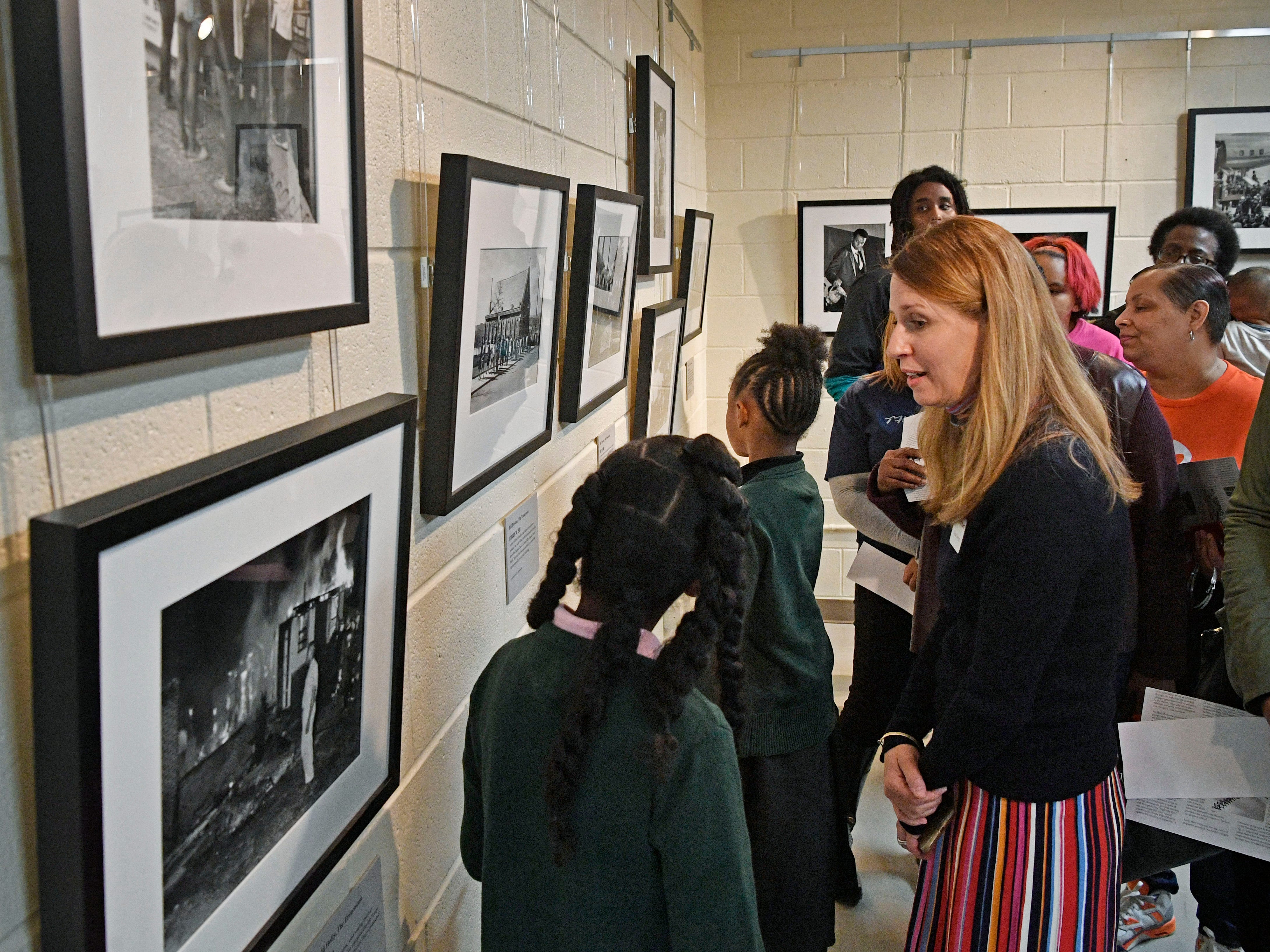 Frist curator Katie Delmez talks with students about photos that are a part of the We Shall Overcome exhibition that was presented at the Robert Churchwell Museum Magnet School. To celebrate its opening, the school hosted an assembly that featured remarks by the principal and a conversation with several participants, including Lajuanda Street Harley, Kwame Lillard, Rip Patton, and Gloria McKissack. Friday Nov. 30, 2018, in Nashville, Tenn.