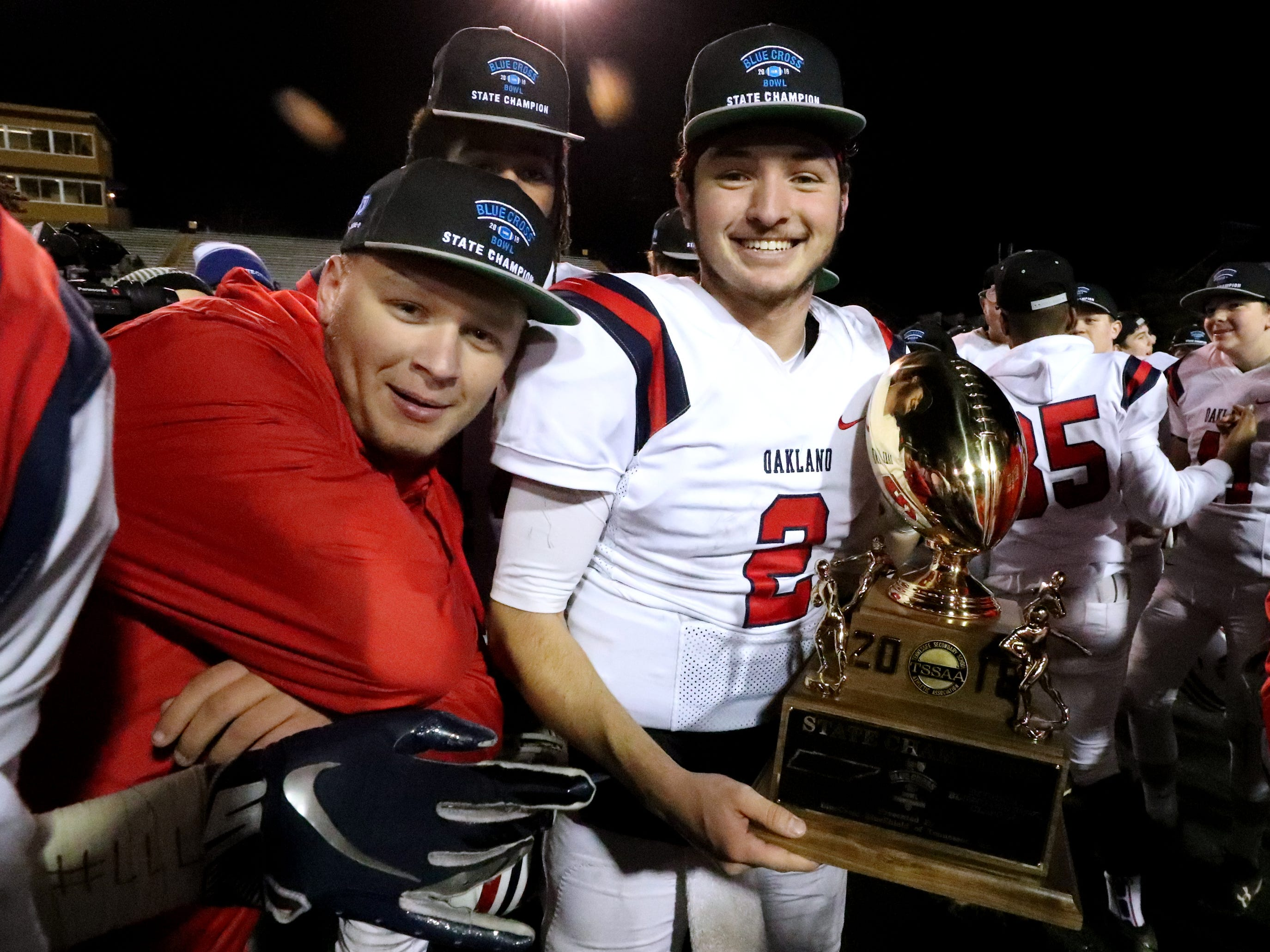 Oakland's manager Avery Watson, left stands next to Oakland's quarterback Brevin Linnell (2) as Linnell holds the state championship trophy after defeating Whitehaven 37-0 during the 6A State Championship BlueCross Bowl game on Thursday, Nov. 29 2018.