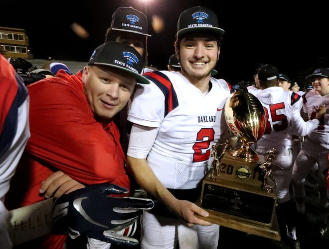 Oakland manager Avery Watson, left, with quarterback Brevin Linnell (2) as Linnell holds the state championship trophy after defeating Whitehaven 37-0 during the Class 6A state championship Thursday.