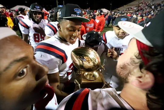 Oakland's Aaron Moore (36) admires the Class 6A state championship trophy after defeating Whitehaven on Thursday.