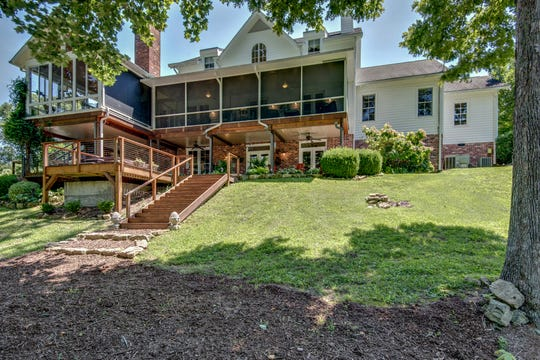 The home for sale on Poor House Hollow Road has multiple patios and decks that maximize the wooded views and privacy.