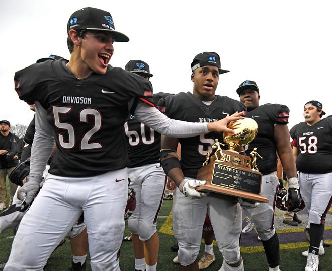 Davidson Academy offensive lineman Eli Litton (52) touches the championship trophy held by Davidson Acad. running back Da'joun Hewitt (5) at the Division II-A BlueCross Bowl state championship at Tennessee Tech's Tucker Stadium in Cookeville, Tenn., on Friday, Nov. 30, 2018.