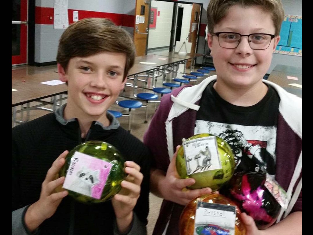 Fairview Middle School art students Landon Bass (left) and Colton Mangrum reveal their ornament during a reception for parents.