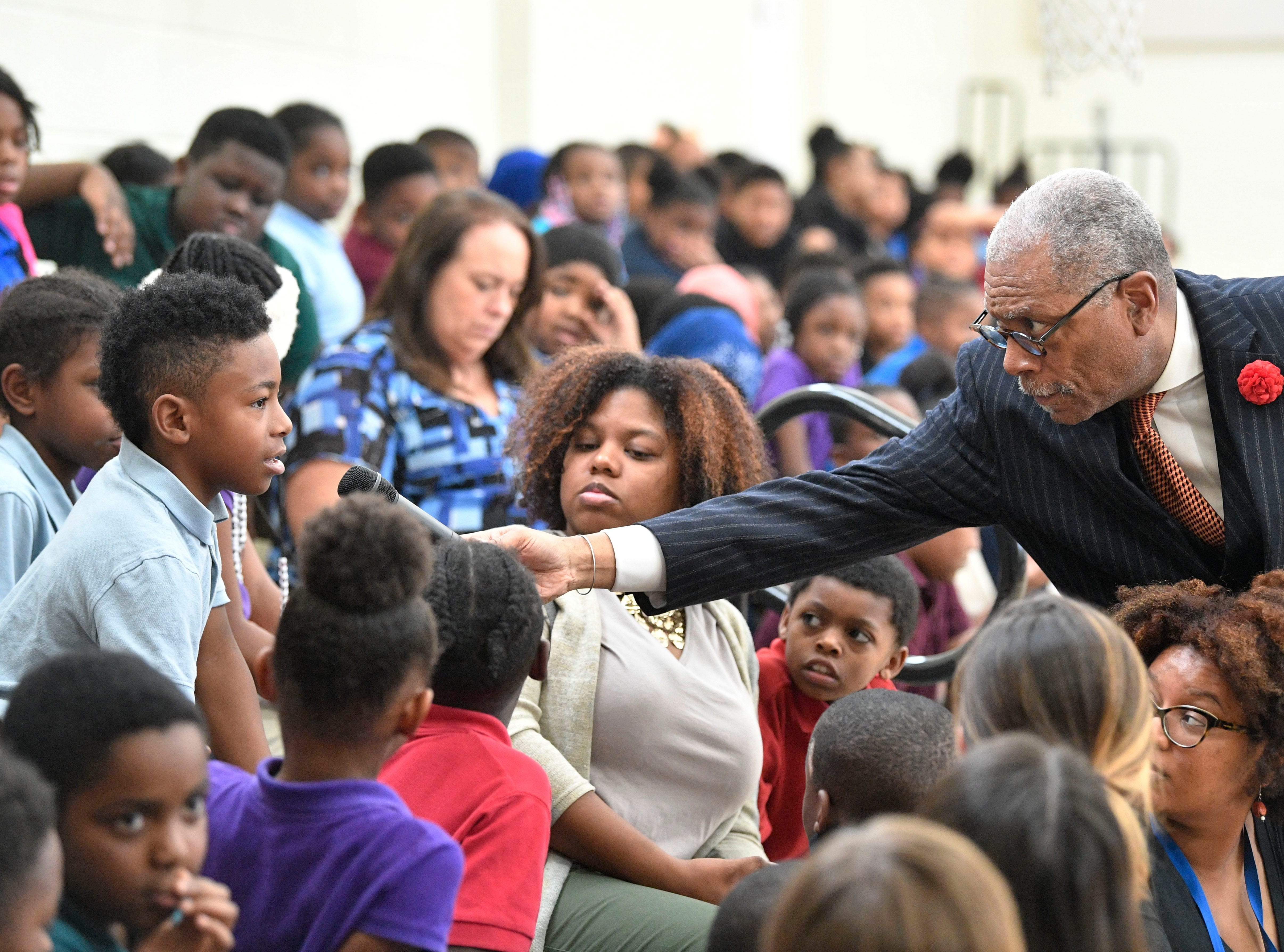 "Robert Churchwell Jr. hold the microphone so a student can ask a question of those on the panel.  A significant part of the Frist Art Museum's ""We Shall Overcome"" photo exhibition will be presented at the Robert Churchwell Museum Magnet School beginning November 30. To celebrate its opening, the school hosted an assembly that featured remarks by the principal and a conversation with several participants, including Lajuanda Street Harley, Kwame Lillard, Rip Patton, and Gloria McKissack.  Friday Nov. 30, 2018, in Nashville, Tenn."