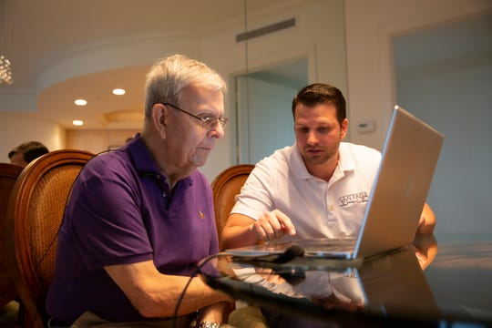 Deed holder George Trepanier, left, works with James Schlimmer, managing partner at Cottrell Title and Escrow on a paperless, digital notarization process, Friday, Nov. 30, 2018 in Bonita Springs.