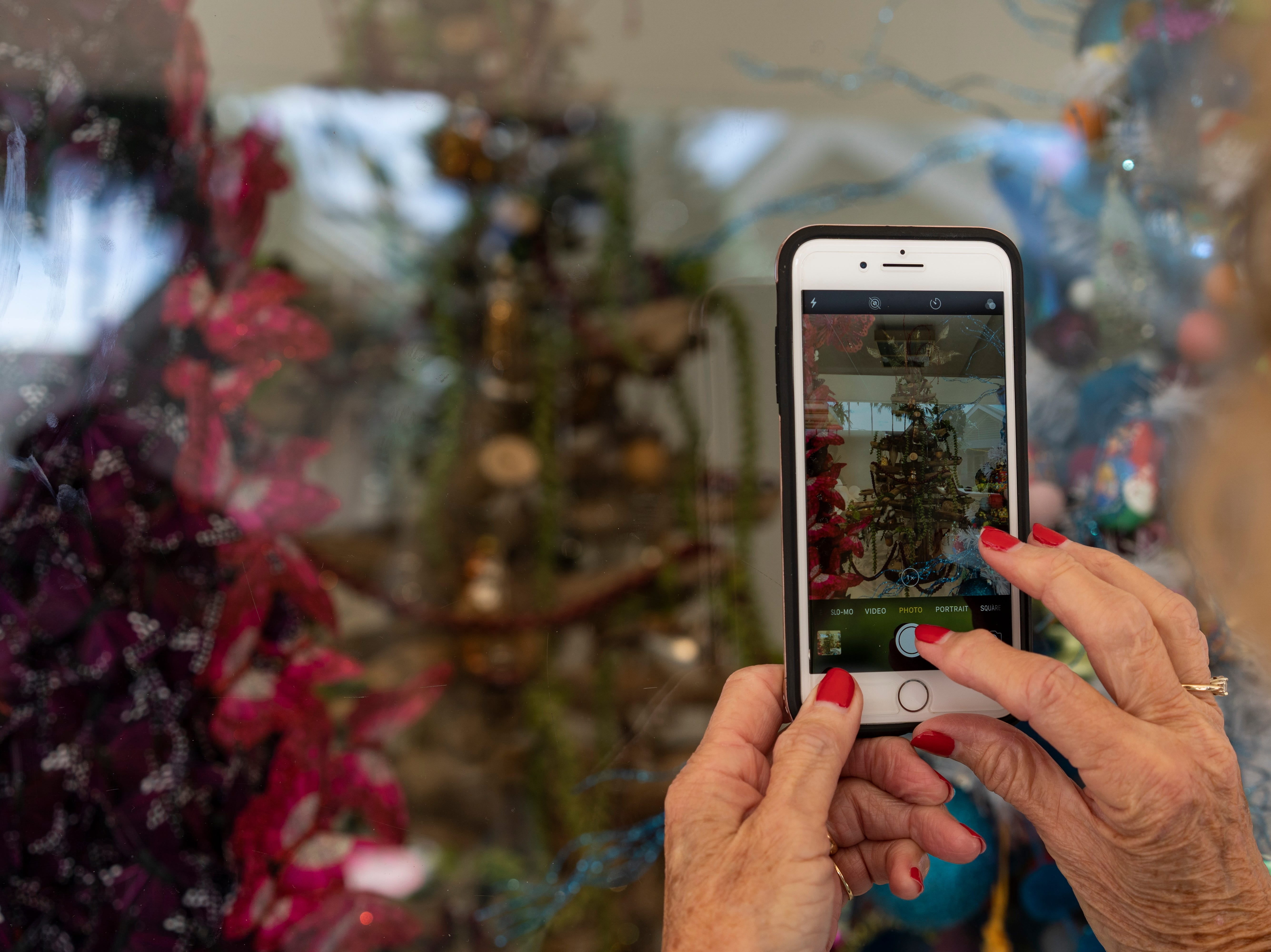 Carol Harnden of Naples takes a photo of the driftwood Christmas tree donated by Tesla to raise funds for Conservancy of Southwest Florida, showcased at the Waterside Shops in Naples. Harnden wanted a photo of the tree to send to her friend in New Hampshire, who is making a driftwood tree as well, Nov. 29, 2018.