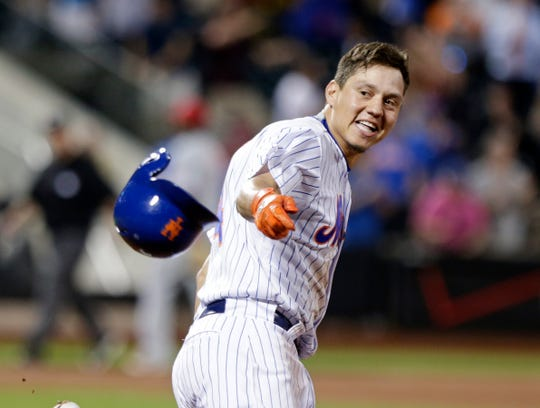 New York Mets' Wilmer Flores (4) tosses his helmet after hitting an hits an RBI single during the tenth inning to win the baseball game against the Philadelphia Phillies Tuesday, May 26, 2015, in New York. The Mets won 5-4.