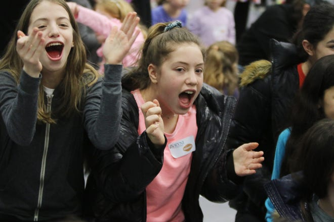 8th graders cheer as they get fired up before the dreidel spin event.