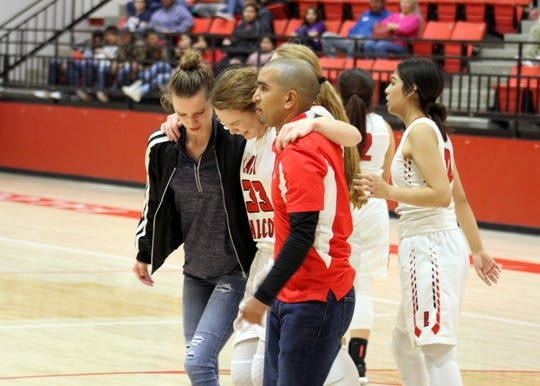 Jayden Ottman is assisted off the court by coach Derrick Martinez and a trainer in the fourth quarter of Thursday's game against Hondo Valley. Ottman finished with seven points.