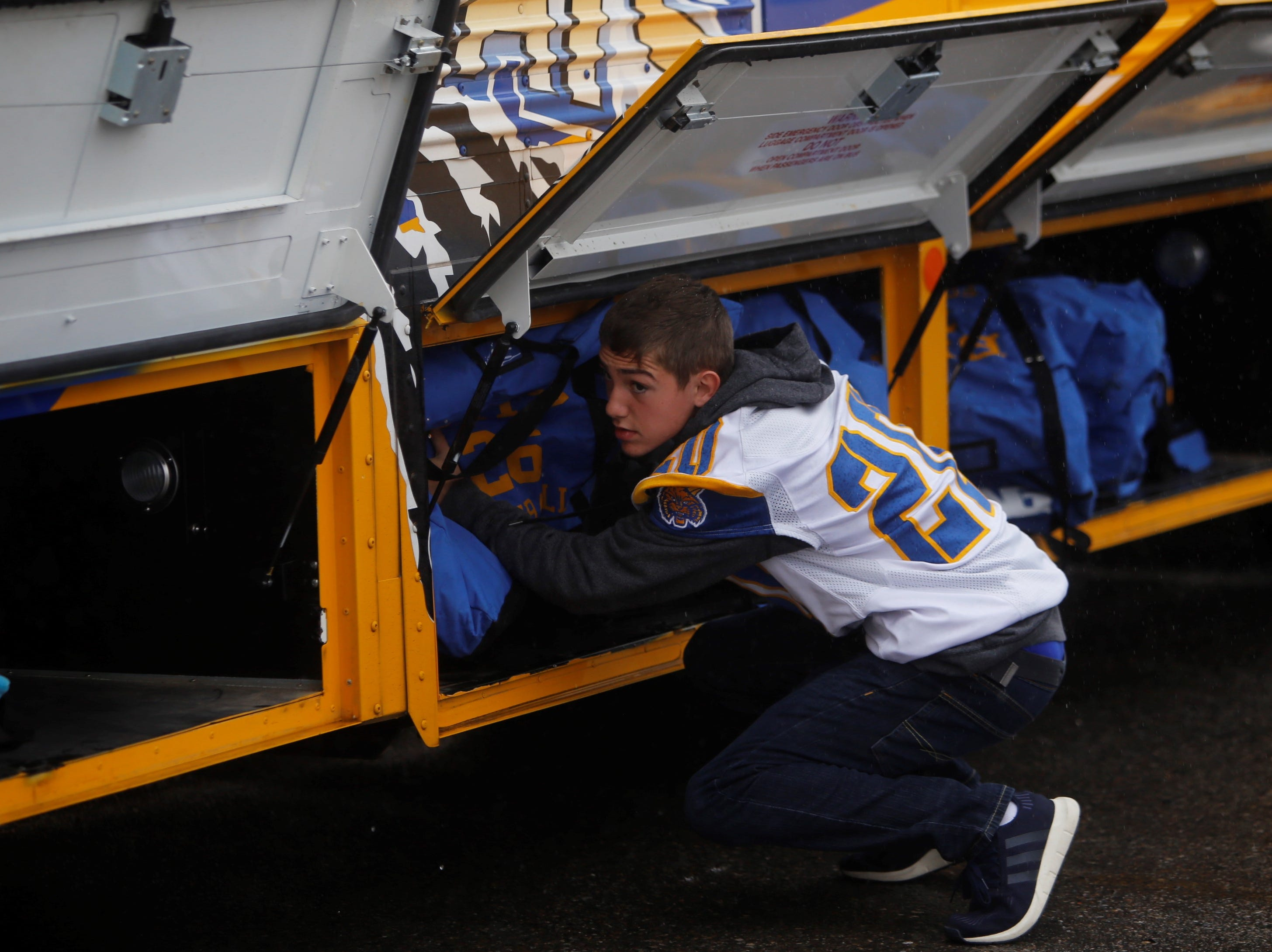 Bloomfield's Anthony Gonzales stashes his gear inside one of the side compartments on the team bus Friday at the Bobcat Stadium parking lot. BHS will play at Taos in Satuarday's 4A state football championship game.