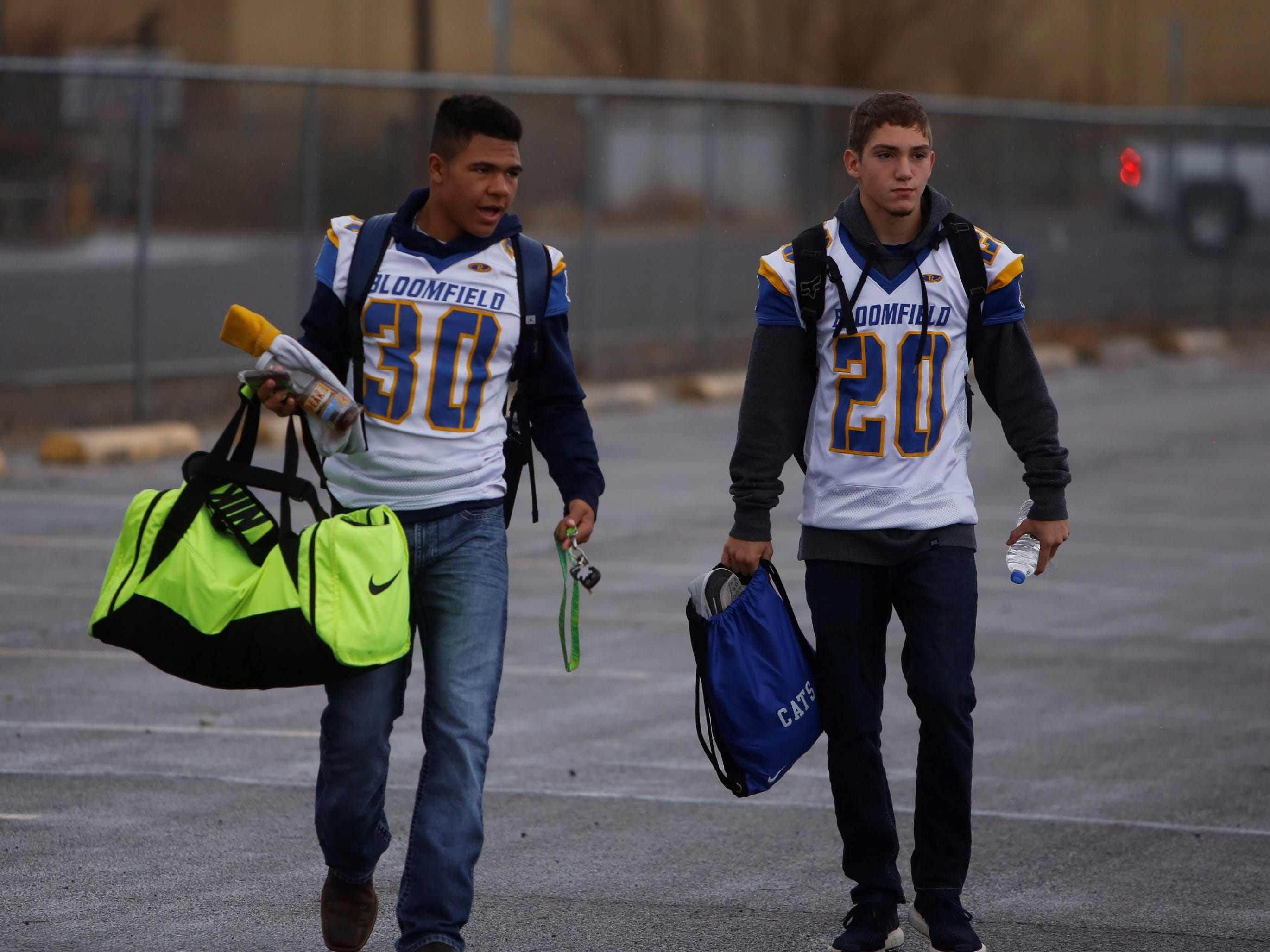 Bloomfield's Kenyon Mosley (30) and Anthony Gonzales (20) arrive at the Bobcat Stadium parking lot to board the team bus for Taos on Friday.