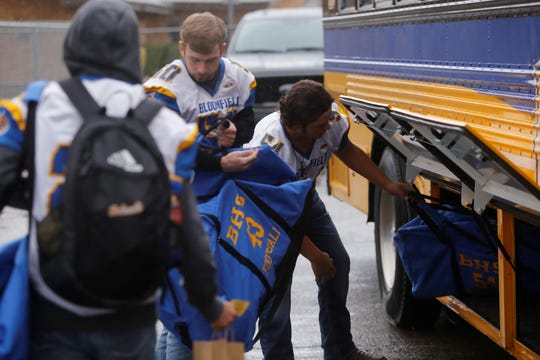 Bloomfield's Aaron Tamporello (50) and Blaze Chavez (54) store their gear inside one of the side compartments on the team bus Friday at the Bobcat Stadium parking lot. BHS will play at Taos in Saturday's 4A state football championship game.
